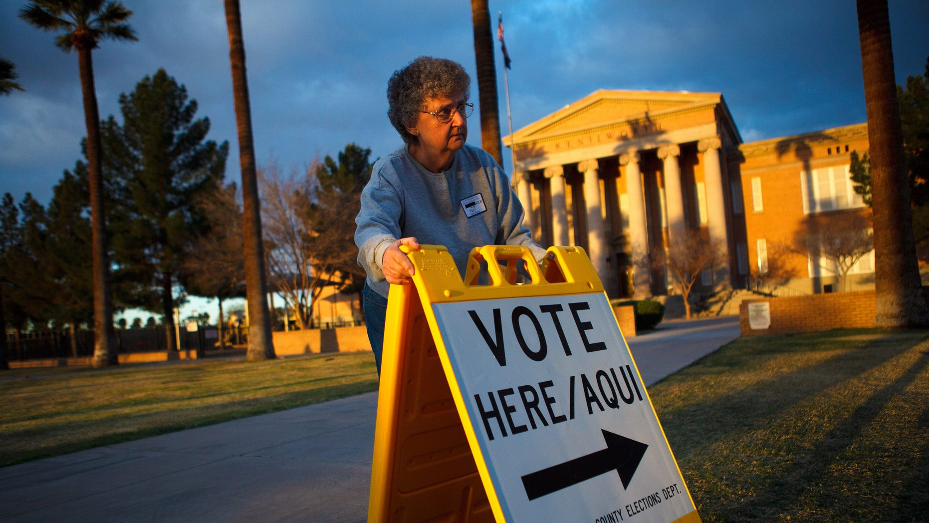 PHOENIX, AZ - FEBRUARY 28:  Election day volunteer Vicki Groff places a sign to direct voters to a polling station at Kenilworth School February 28, 2012 in Phoenix, Arizona. Voters in this state participate in choosing who will be the Republican candidate to contest President Barack Obama in the general election.  (Photo by Jonathan Gibby/Getty Images)
