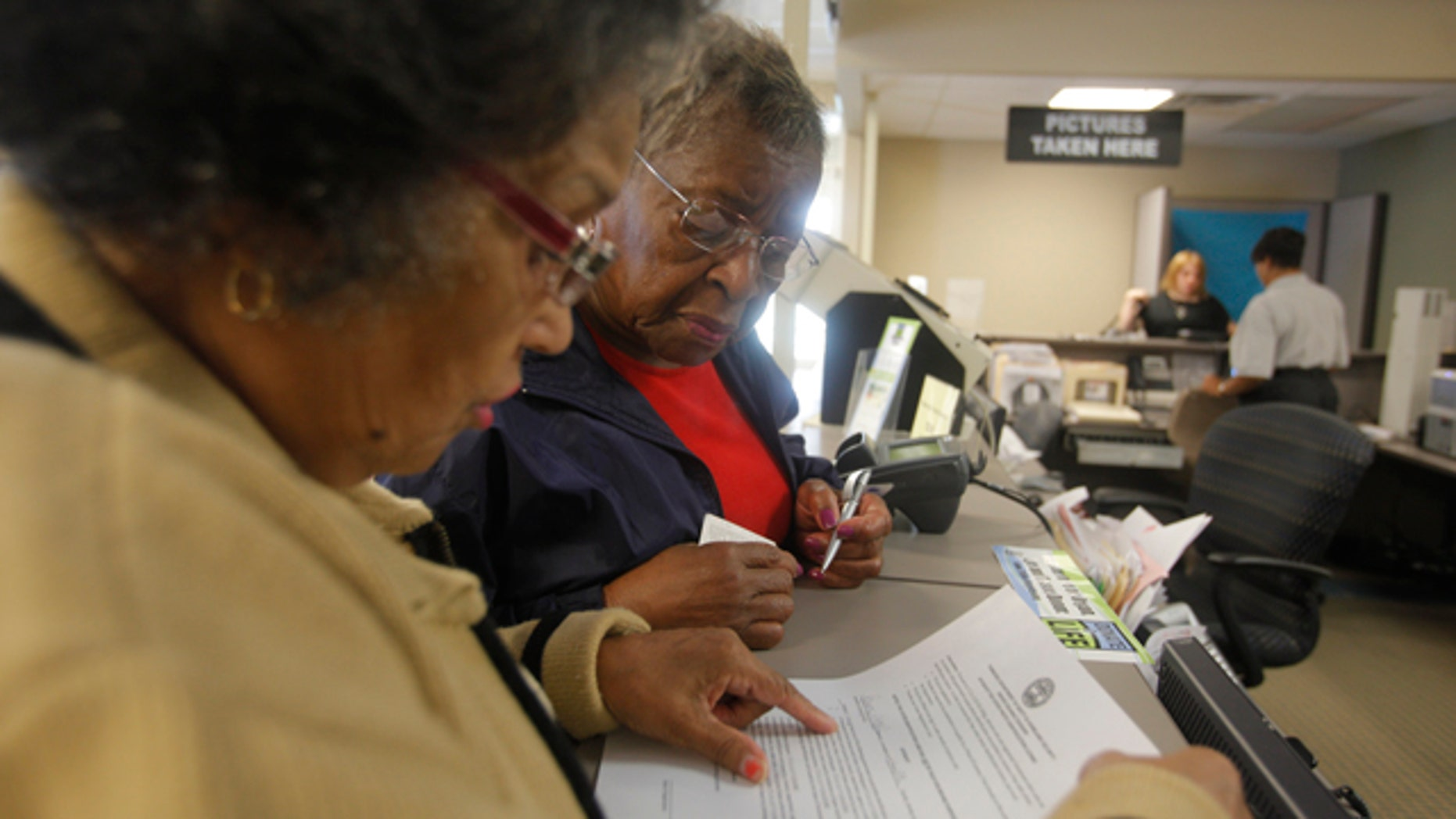 FILE: Sept. 19, 2011: Dorothy Melvin, center, gets help in Tennessee from Charline Kilpatrick in getting a license with a photograph, which will be valid at polling stations.
