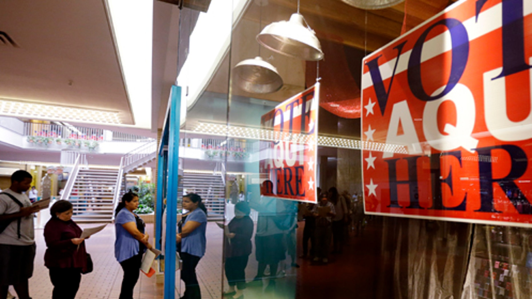 Voters wait in line at a polling place located inside a shopping mall on Election Day, 2012, in Austin, Texas.