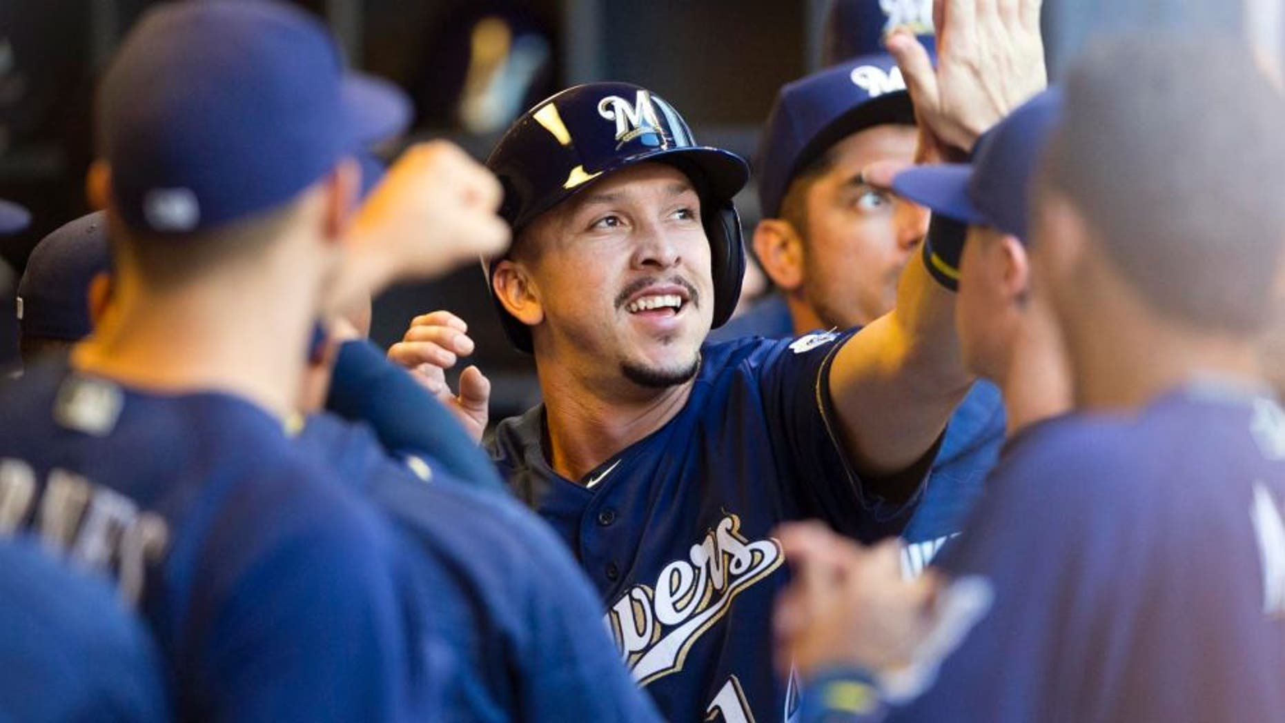 Monday, Aug 8, 2016: Milwaukee Brewers third baseman Hernan Perez high fives teammates in the dugout after scoring during the second inning against the Atlanta Braves at Miller Park. The Brewers lost 4-3.