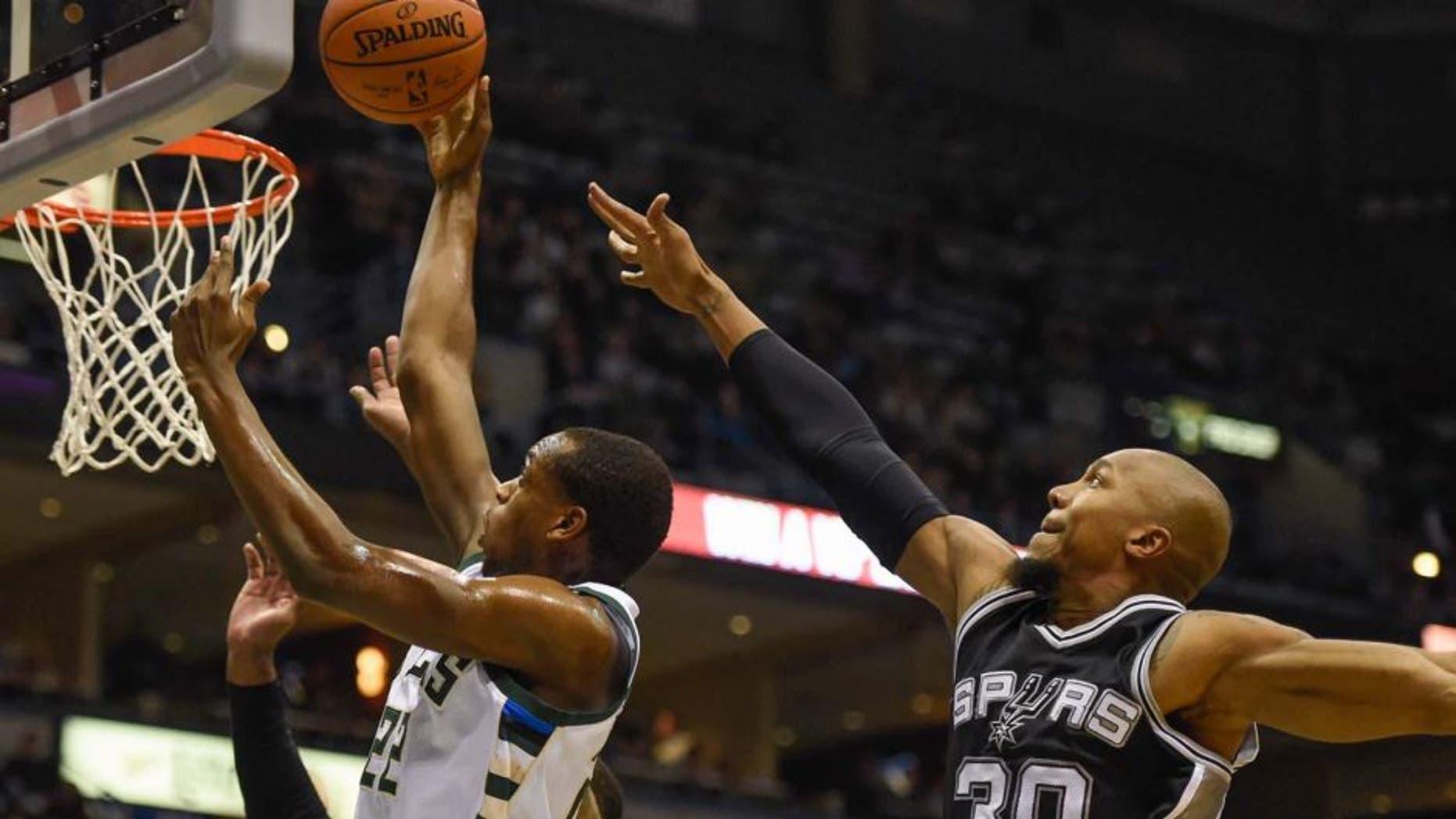 Monday, Jan. 4: Milwaukee Bucks guard Khris Middleton (left) takes a shot against San Antonio Spurs forward David West in the first quarter at BMO Harris Bradley Center in Milwaukee, Wis.