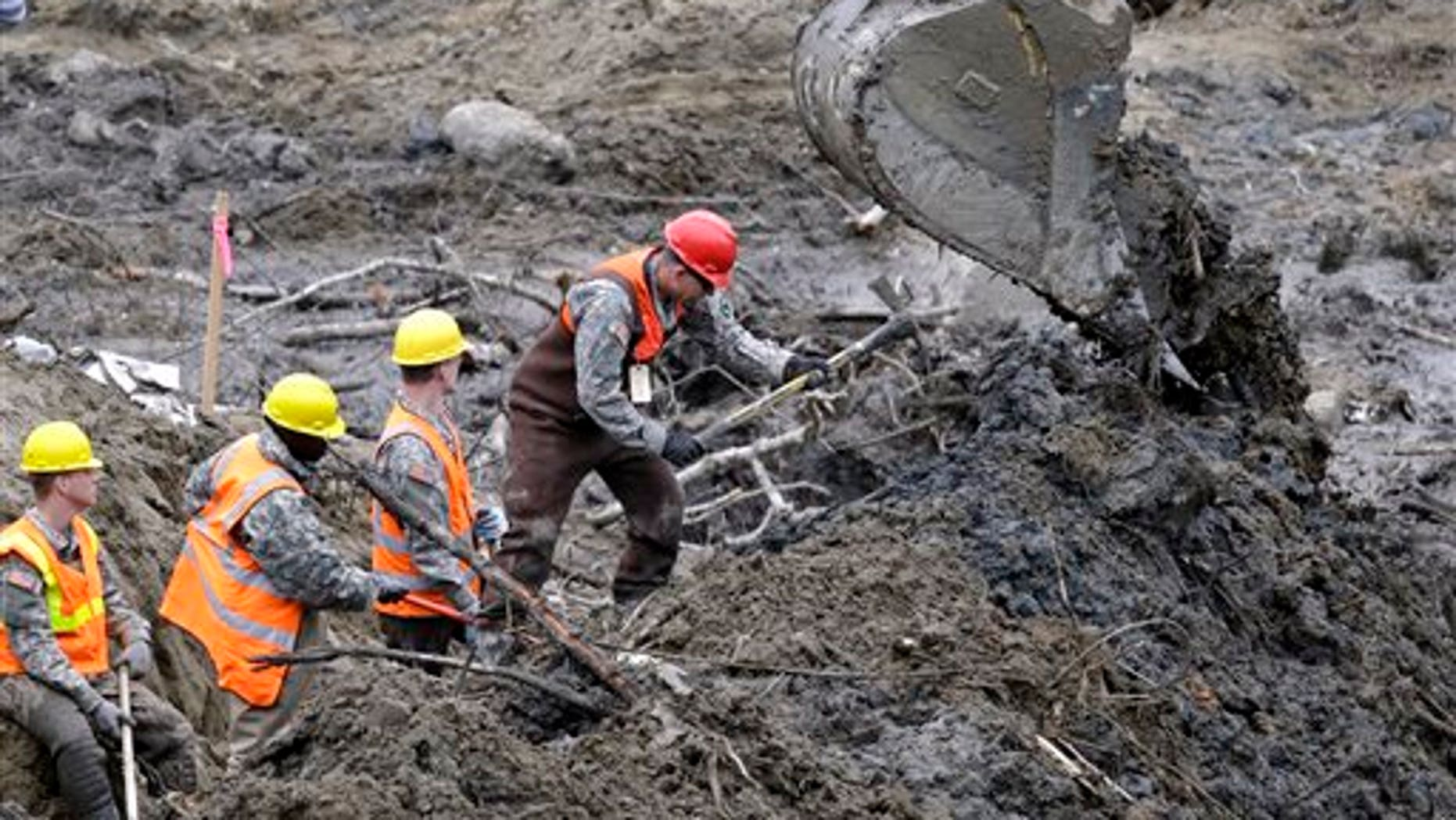 Workers use hand tools next to heavy equipment at the scene of a deadly mudslide in Oso, Wash., earlier this month.