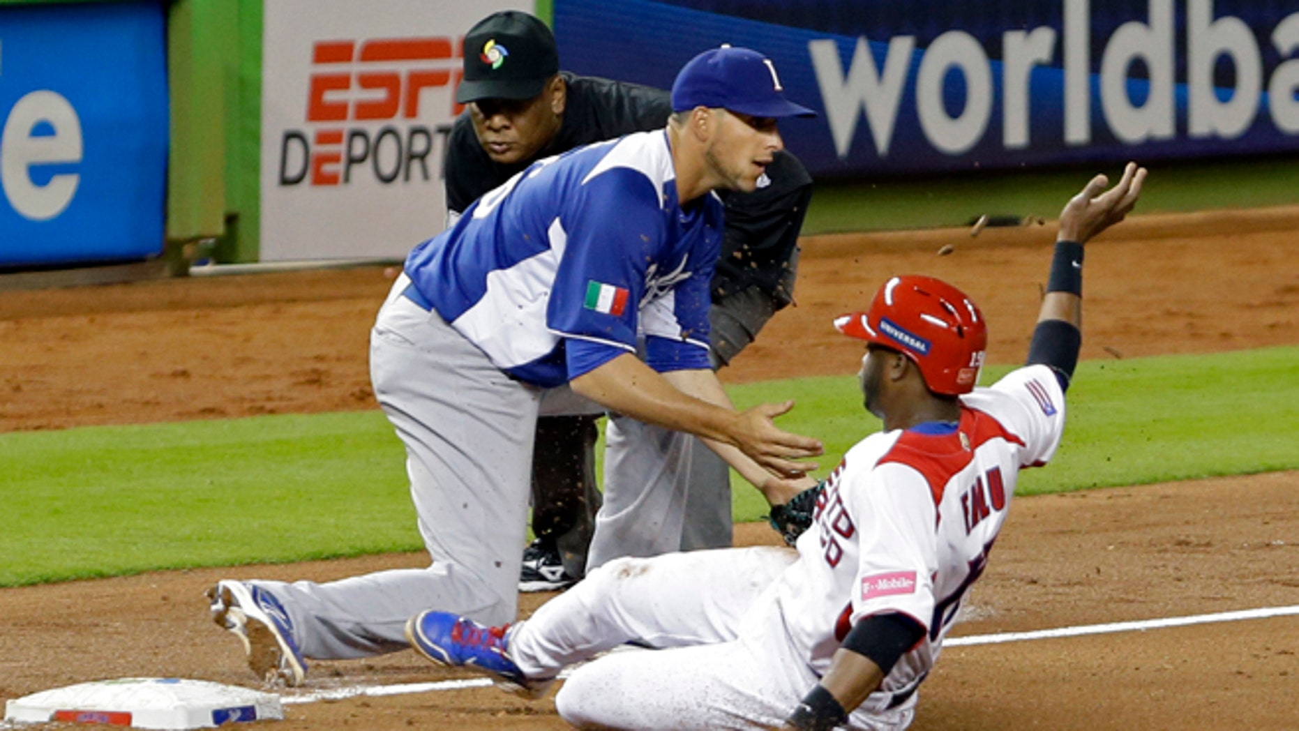 Puerto Rico's Irving Falu slides safely into third on a base hit by teammate Yadier Molina as Italy third baseman Alex Liddi awaits the late throw during the fourth inning of a second-round elimination game of the World Baseball Classic in Miami, Wednesday, March 13, 2013. Third base umpire Edgar Estivison watches the play. (AP Photo/Wilfredo Lee)