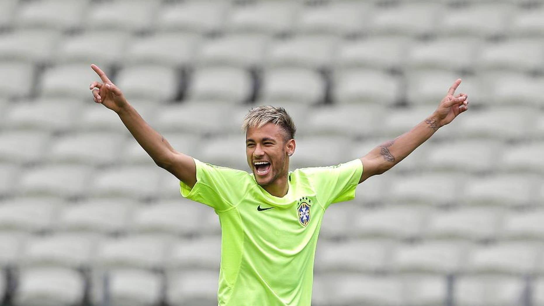 FILE - This June 16, 2014 file photo shows Brazil's Neymar smiling as he holds out his arms during a training session at the Arena Castelao in Fortaleza, Brazil. Through one week of the World Cup, Facebook has already seen more people having more interactions about the tournament on the social media site than it had for the Sochi Olympics, Super Bowl and Academy Awards combined. A photo posted by Pitbull, who performed at the opening ceremonies, has received more than 1.2 million interactions, as has a photo posted by Brazilian soccer star Neymar, Facebook said. (AP Photo/Andre Penner)