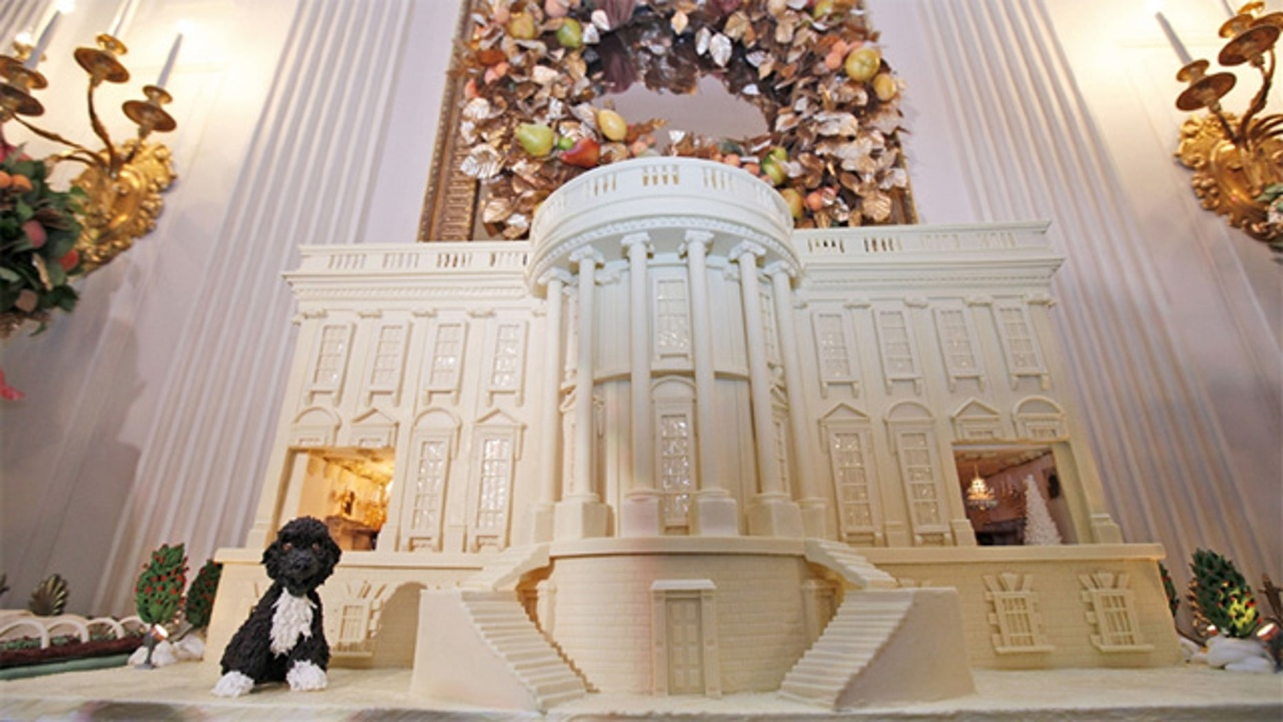 Dec. 1., 2011: A miniature of the Obama family's dog, Bo, sits on a 400-pound white chocolate-covered gingerbread replica of the White House in the State Dining Room of the White House in Washington, DC.