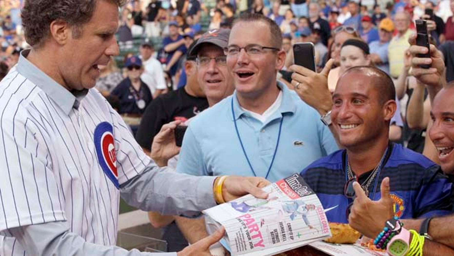 FILE - Will Ferrell, left, talks with fans after throwing out the ceremonial first pitch before a baseball game between the Miami Marlins and the Chicago Cubs in Chicago.