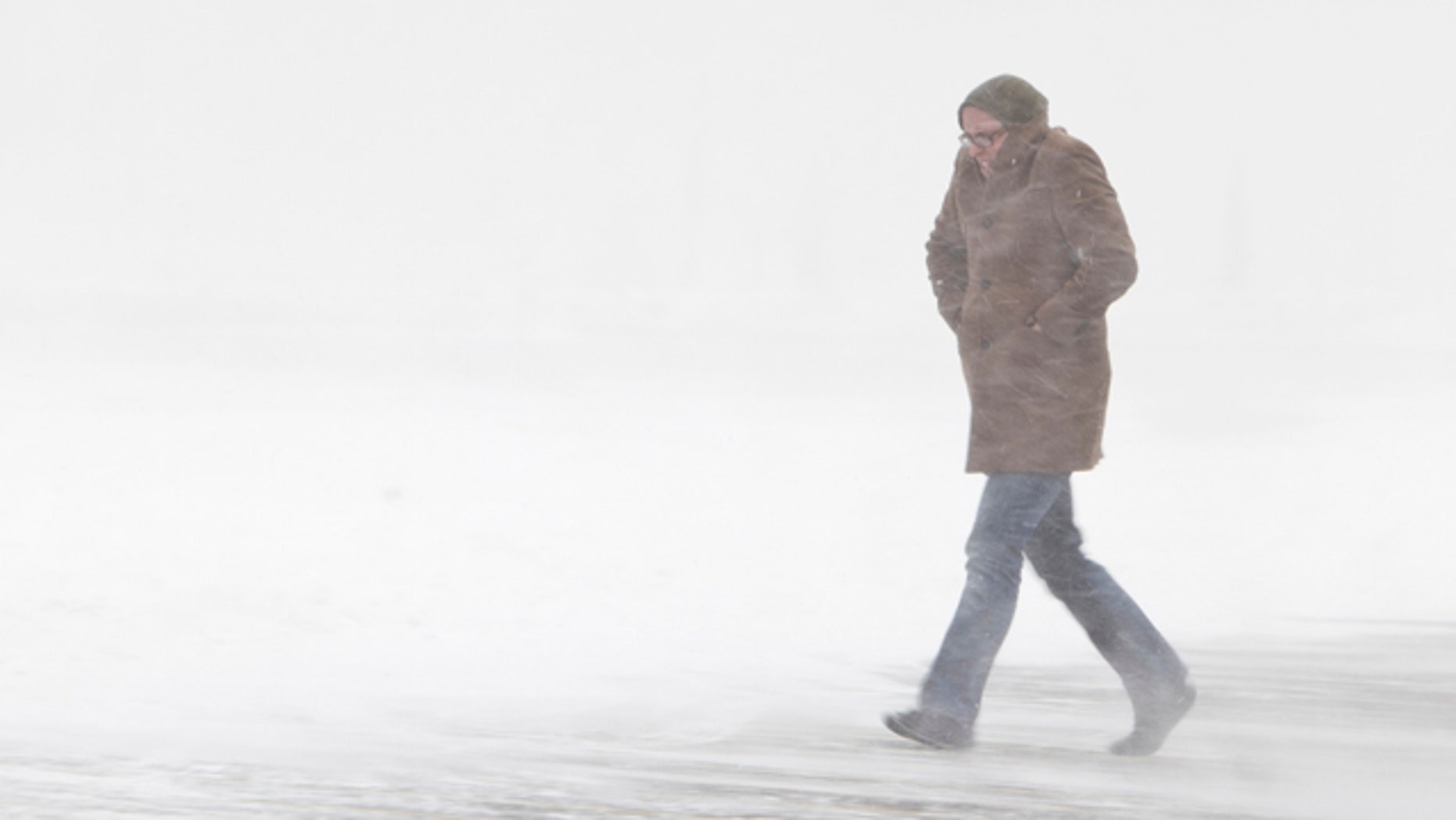 A shopper walks in the parking lot of a store amid blowing snow, in Omaha, Neb.