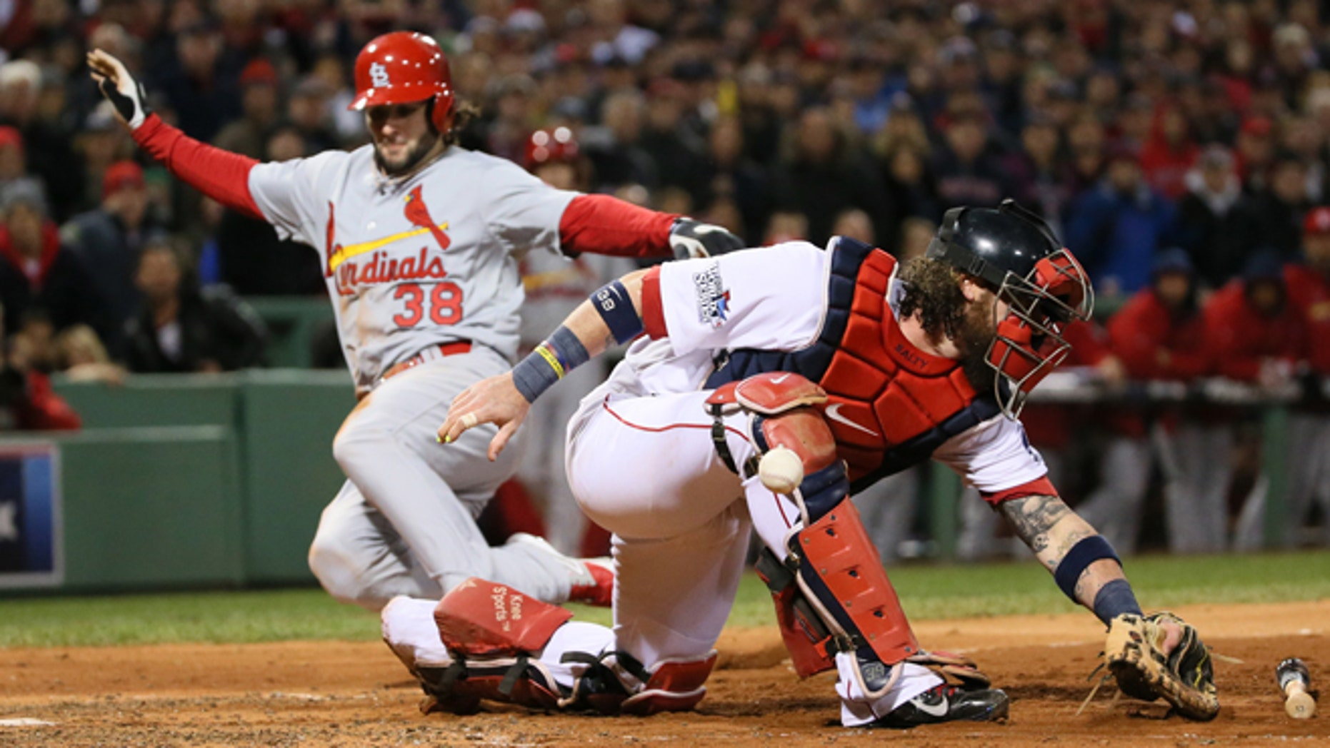 Oct. 24, 2013: Boston Red Sox catcher Jarrod Saltalamacchia is unable to handle the throw from left fielder Jonny Gomes as St. Louis Cardinals pinch runner Pete Kozma scores on a sacrifice fly by Matt Carpenter in the seventh inning during Game 2 of the World Series between the St. Louis Cardinals and the Boston Red Sox at Fenway Park in Boston. Pitcher Craig Breslow backing up the play threw wildly to third for an error, allowing Jon Jay to also score on the play. (AP/St. Louis Post-Dispatch, Chris Lee)