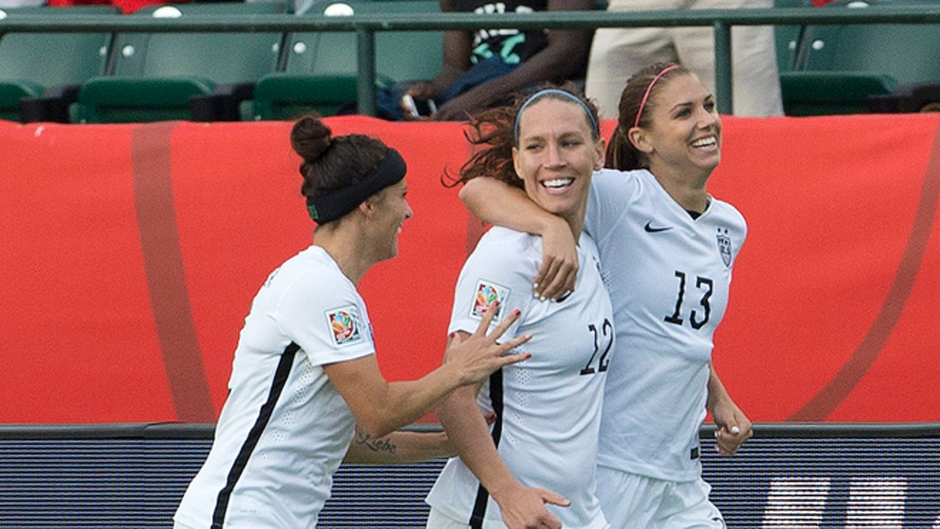 United States' Ali Krieger (11), Lauren Holiday (12) and Alex Morgan (13) celebrate a goal against Colombia during second half FIFA Women's World Cup round of 16 soccer action in Edmonton, Alberta, Canada, Monday, June 22, 2015.  (Jason Franson/The Canadian Press via AP) MANDATORY CREDIT
