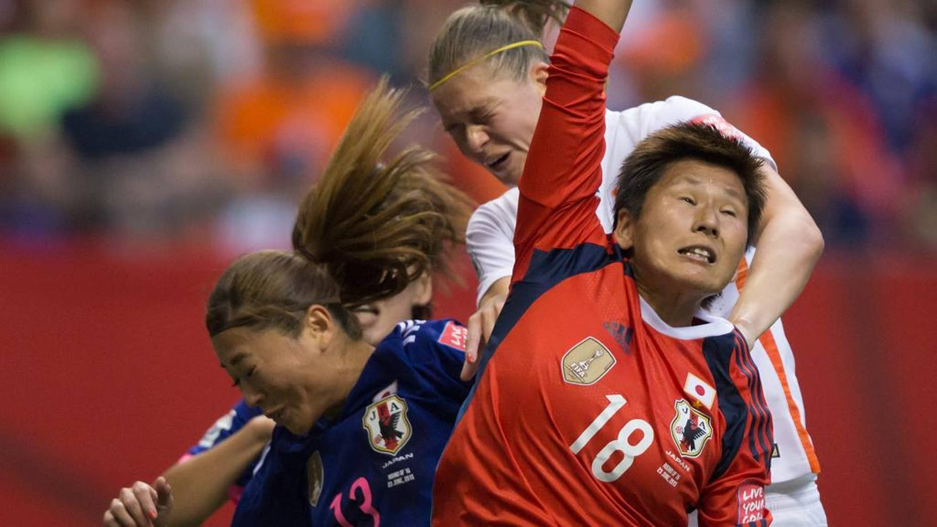 Netherlands' Anouk Dekker, back right, gets her head on the ball but fails to score as Japan goalkeeper Ayumi Kaihori (18) reaches for the ball and Rumi Utsugi (13) defends during the second half of a round of 16 soccer match at the FIFA Women's World Cup, Tuesday, June 23, 2015, in Vancouver, British Columbia, Canada. (Darryl Dyck/The Canadian Press via AP)