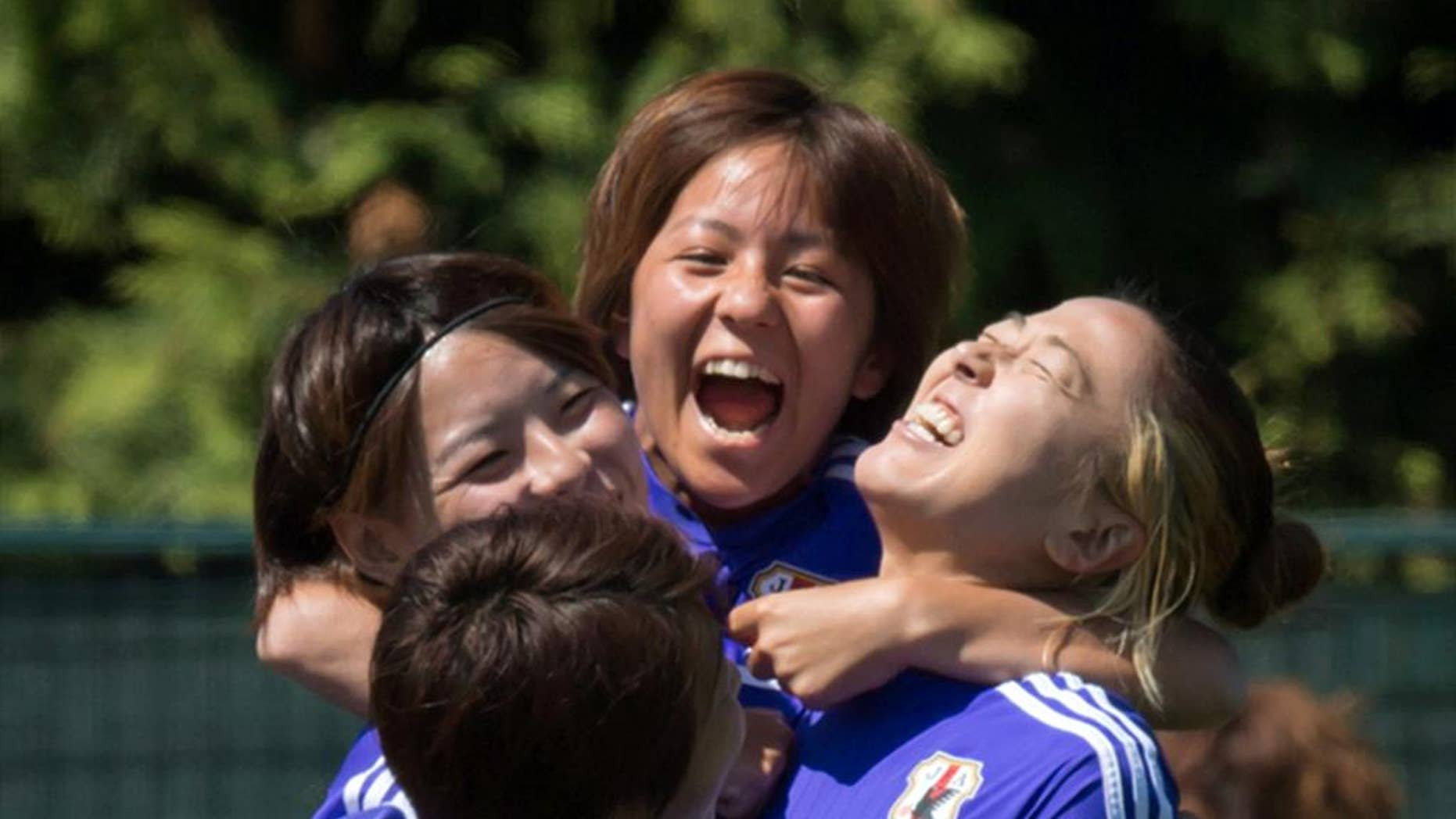Japan's Mana Iwabuchi, back, jumps onto teammates Aya Sameshima, back left, Yuki Ogimi, right, and Aya Miyama, front, during a practice session in Vancouver, British Columbia, in Canada, on Saturday, July 4, 2015. Japan and the United States are scheduled to play in the final of the FIFA Women's World Cup soccer tournament on Sunday in Vancouver. (Darryl Dyck/The Canadian Press via AP) MANDATORY CREDIT