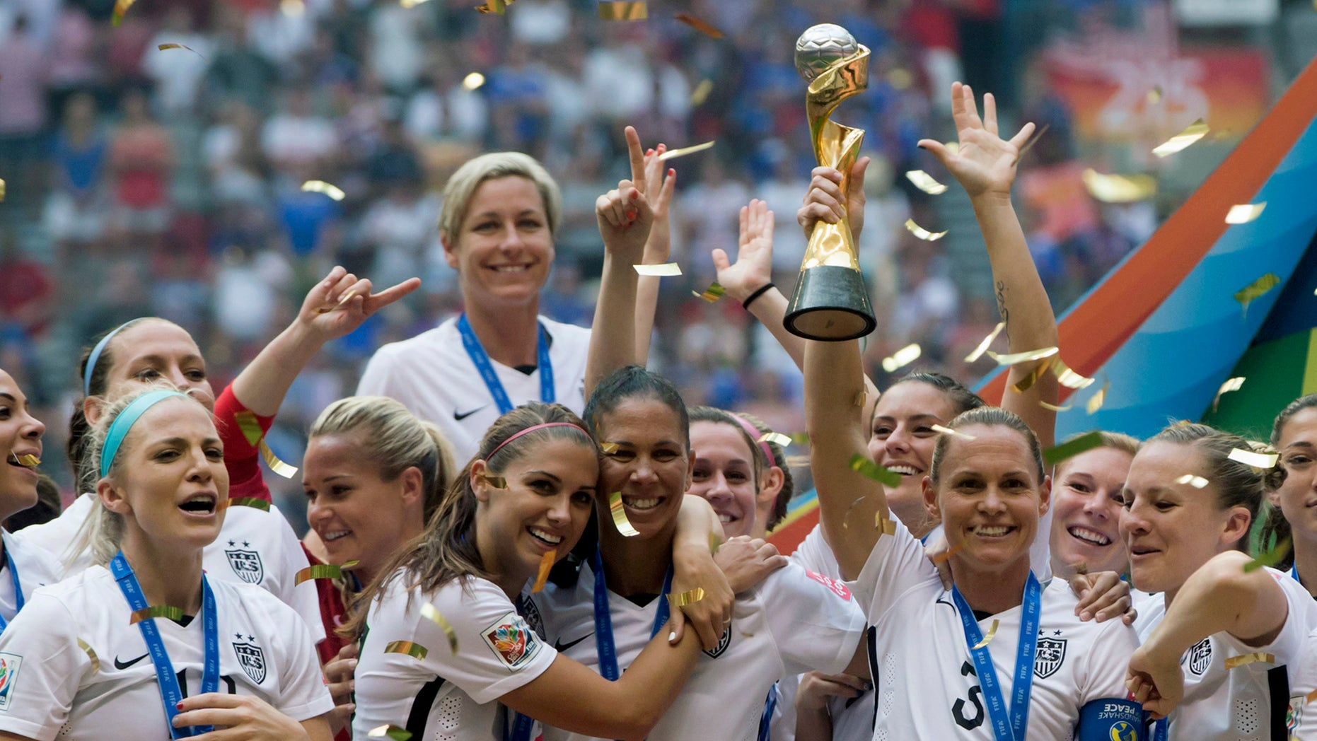 The United States Women's National Team celebrates with the trophy after they defeated Japan 5-2 in the FIFA Women's World Cup soccer championship in Vancouver, British Columbia, Canada, Sunday, July 5, 2015. (Darryl Dyck/The Canadian Press via AP) MANDATORY CREDIT