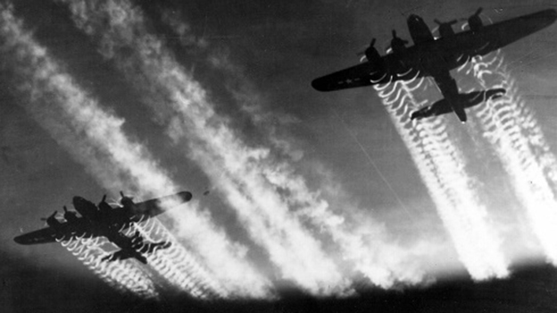 Contrails from two B-17 Flying Fortress aircraft streak across the sky.