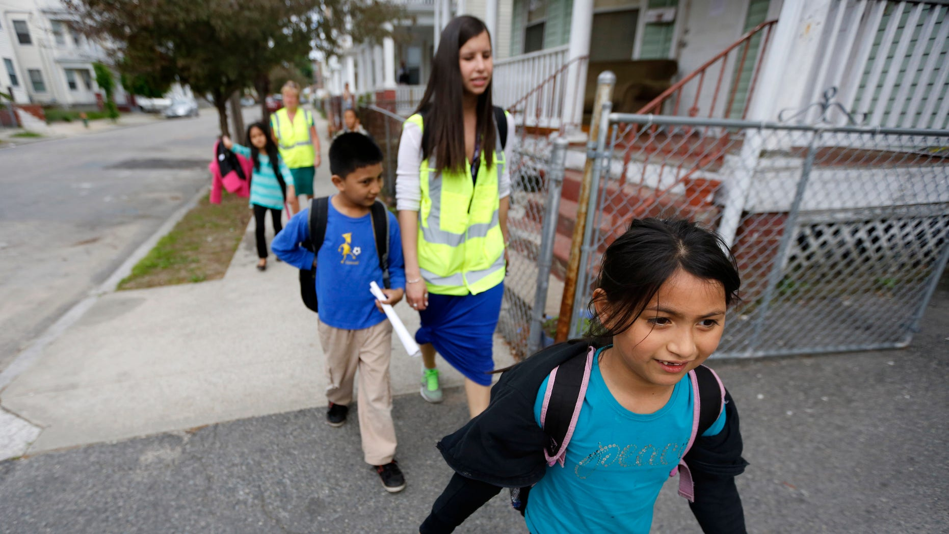 Divya Dahal, 8, walks home from school with a group of grade school children escorted by Allyson Trenteseaux, a Walking School Bus program manager, center right, in Providence, R.I. (AP Photo/Steven Senne)