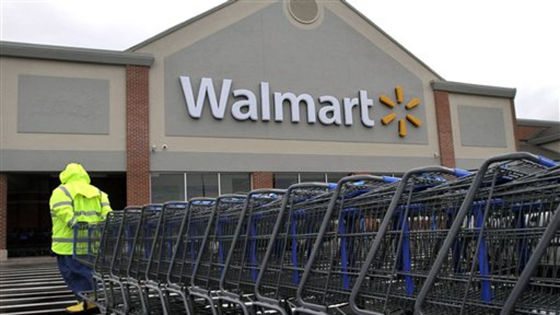 Nov. 13, 2012: A worker pulls a line of shopping carts toward a Walmart store in North Kingstown, R.I. Wal-Mart Stores Inc. reported a 9 percent increase in net income for the third quarter, but revenue for the world's largest retailer fell below Wall Street forecasts as its low-income shoppers continue to grapple with an uncertain economy.