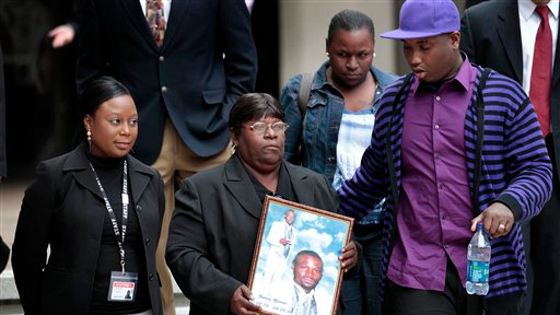 March 31: Edna Glover, mother of Henry Glover, leaving Federal Court holding his photo after the sentencing of two New Orleans police offers in his death.