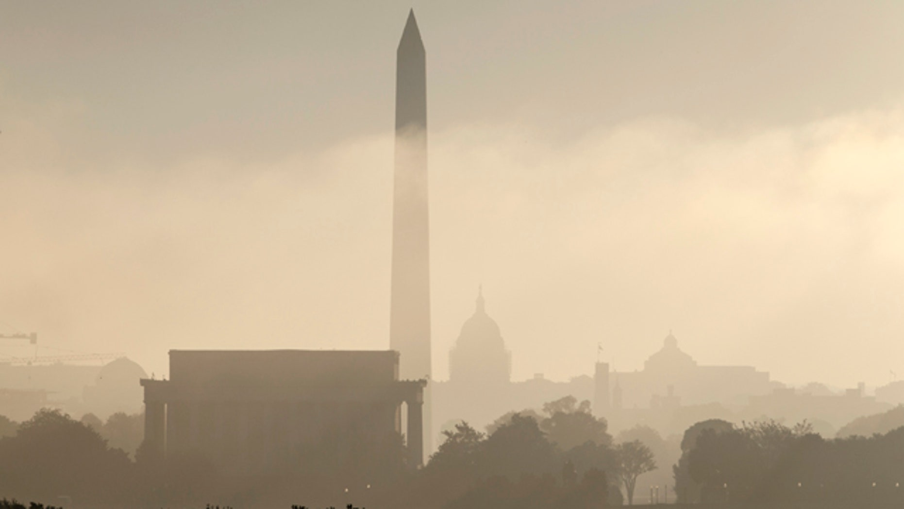 FILE- In this Sept. 26, 2014, photo, the monuments of Washington are silhouetted through the lifting fog over the nation's capitol as seen from an overlook in Arlington, Va. From left are, the Lincoln Memorial, Washington Monument, the Capitol, the Smithsonian Castle, and the Library of Congress. (AP Photo/J. Scott Applewhite, File)