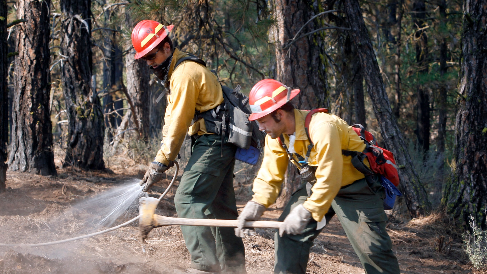 September 10: Alex George, left, and Kevin Weed of Glacier Peak Wildfire, Inc., extinguish hot spots along a fire line near Box Canyon Road on the eastern boundary of the Monastery Complex Fire in Yakima, Washington.