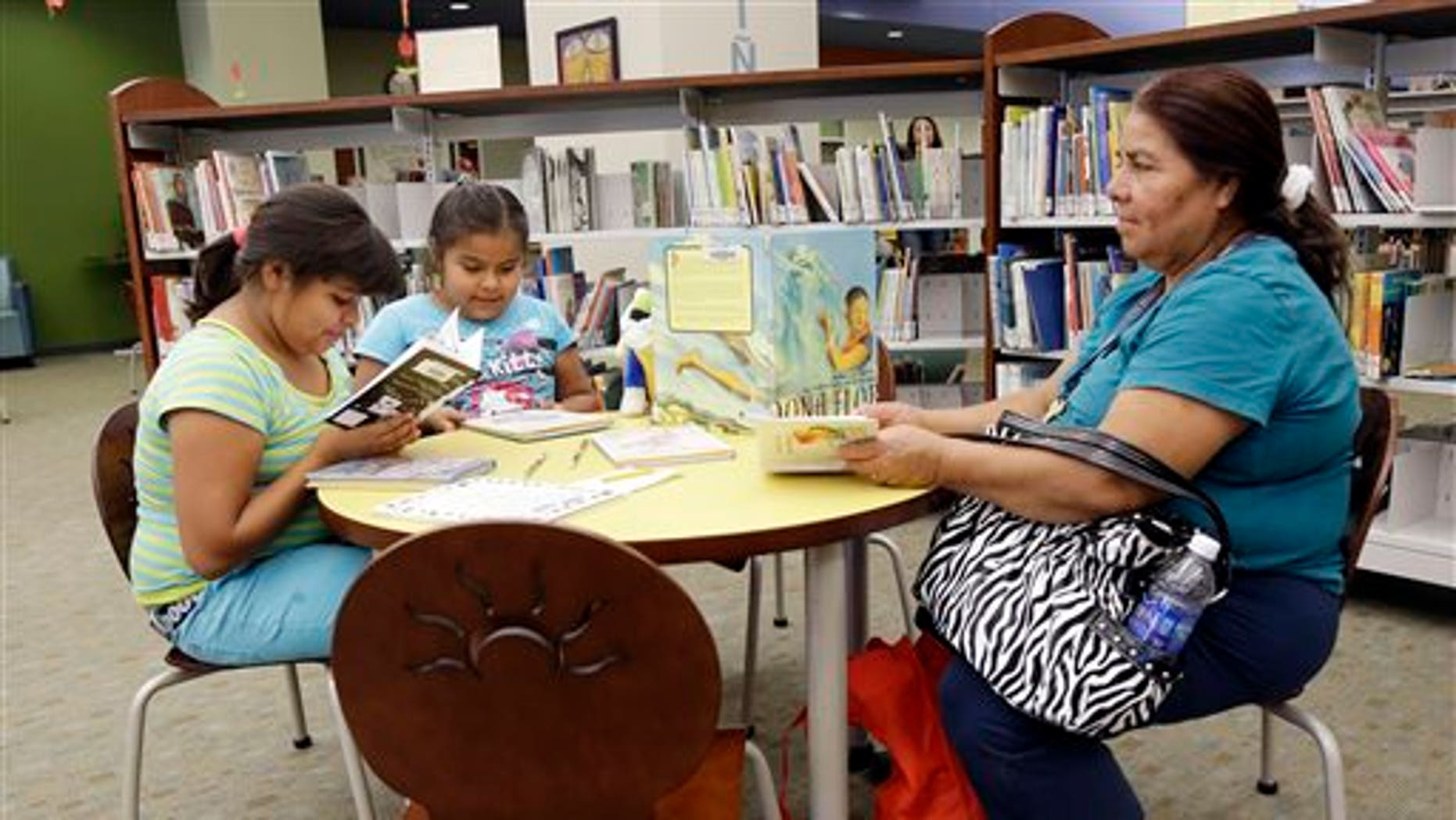 In this Friday, July 19, 2013 photo, Maria Lopez, right, reads in the city library alongside daughters Emily, 9, at left, and Esmeralda, 7, in Watsonville, Calif. In the bricked plaza, strolling musicians wearing glitzy cowboy outfits blast a mariachi song, while Spanish-speaking shoppers bustle between farm stands choosing tasty cactus leaves and fresh chiles. Welcome to an increasingly typical town in California, a state where Hispanics become the largest ethnic group this summer. As the Golden State becomes less and less white, communities are becoming more segregated, not less. (AP Photo/Marcio Jose Sanchez)
