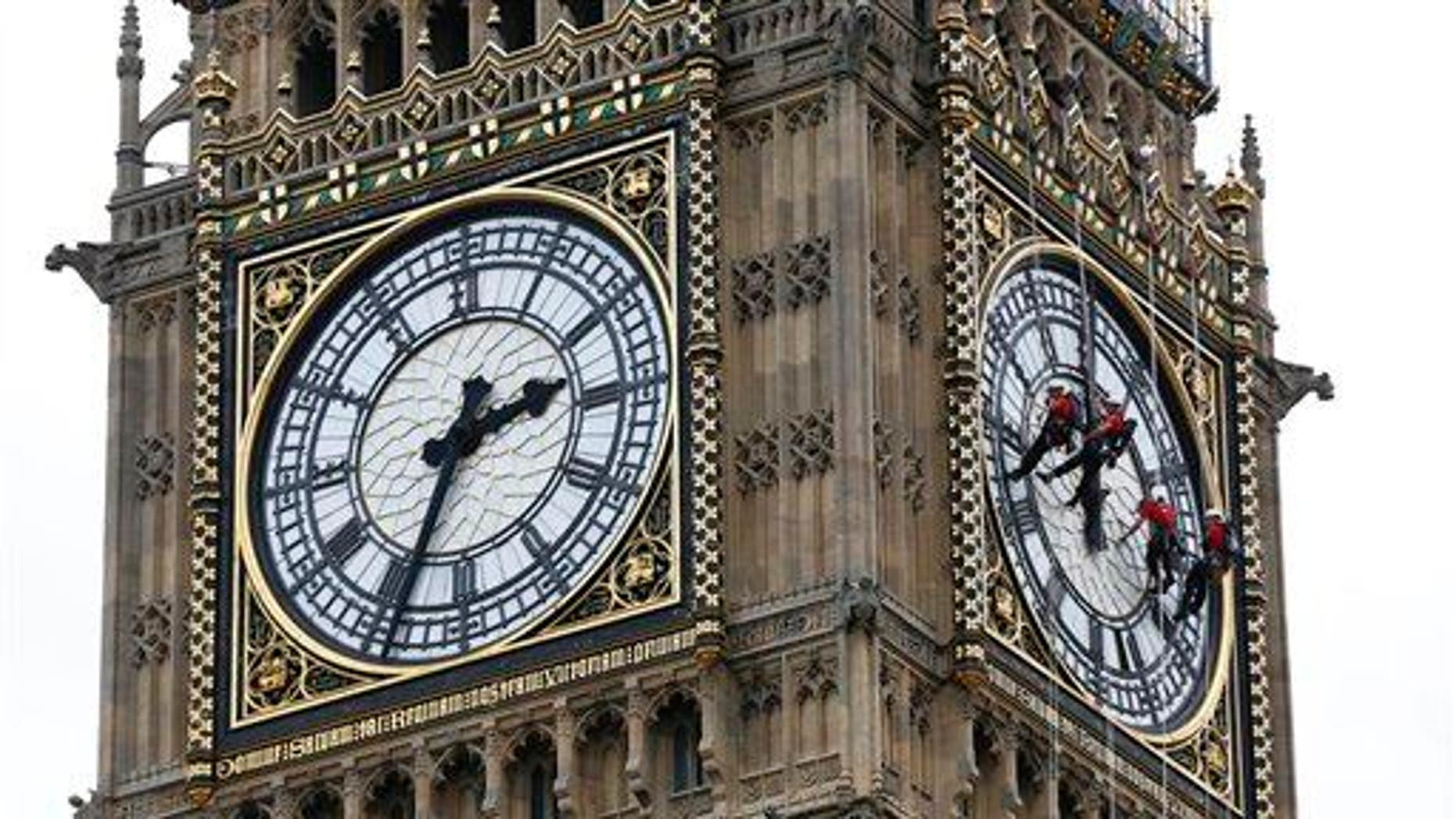Workers clean the face of Big Ben in London.