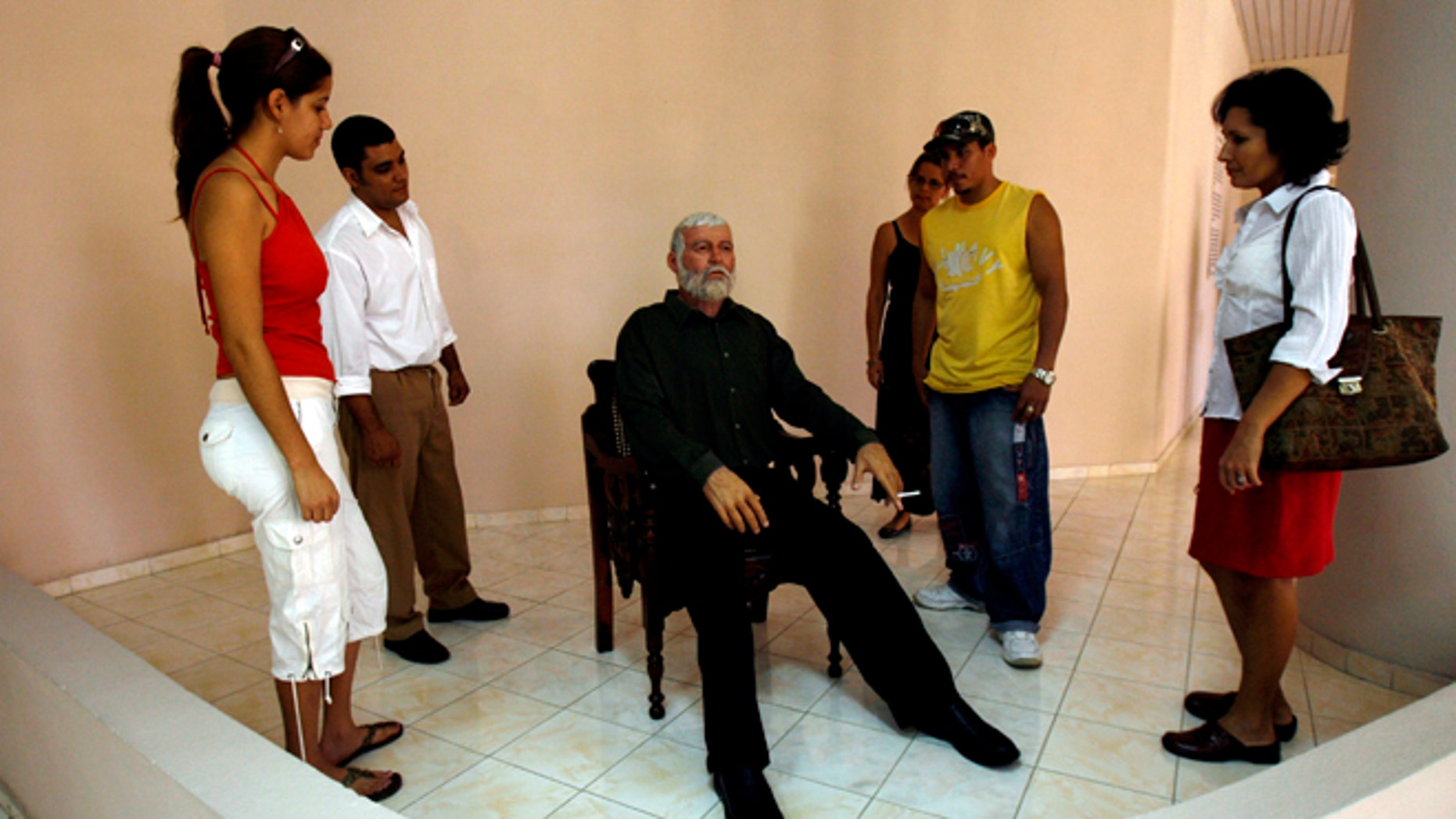 FILE - In this Feb. 2, 2010 file photo, visitors look at a wax figure of U.S. writer Ernest Hemingway at an exhibition in the wax museum at Bayamo, Cuba. Hemingway lived in Cuba on and off for years and worked on some of his most famous books there, including For Whom the Bell Tolls and The Old Man and the Sea. (AP Photo/Ismael Francisco, Prensa Latina, File)