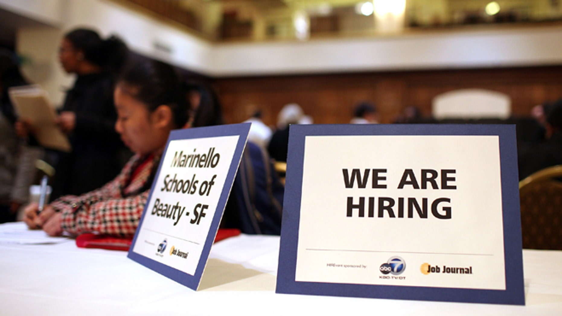 """SAN FRANCISCO, CA - MARCH 27:  A """"we are hiring"""" sign is displayed on a table during the San Francisco Hirevent job fair at the Hotel Whitcomb on March 27, 2012 in San Francisco, California. As the national unemployment rate stands at 8.3 percent, job seekers turned out to meet with recruiters at the San Francisco Hirevent job fair where hundreds of jobs were available.  (Photo by Justin Sullivan/Getty Images)"""