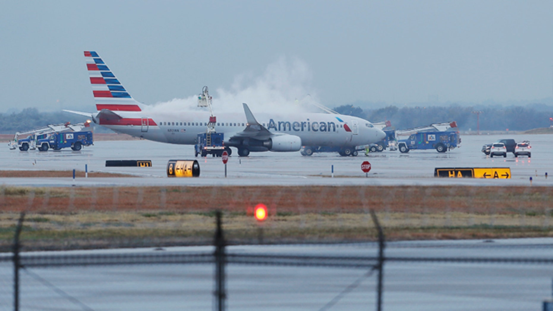 Crews spray deicing solution onto an American Airlines 737 before departure at Dallas-Fort Worth International airport, Monday, Nov. 25, 2013. Winter weather has caused travel disruptions throughout the area including the cancellation and delays of hundreds of flights. (AP Photo/Brandon Wade)