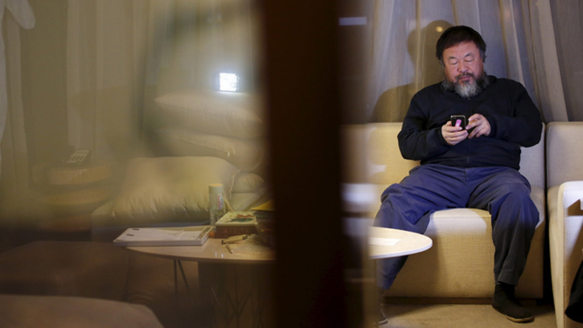 March 24: Dissedent Chinese artist Ai Weiwei uses his mobile phone at an interview with Reuters at the hotel he is staying at in Beijing.