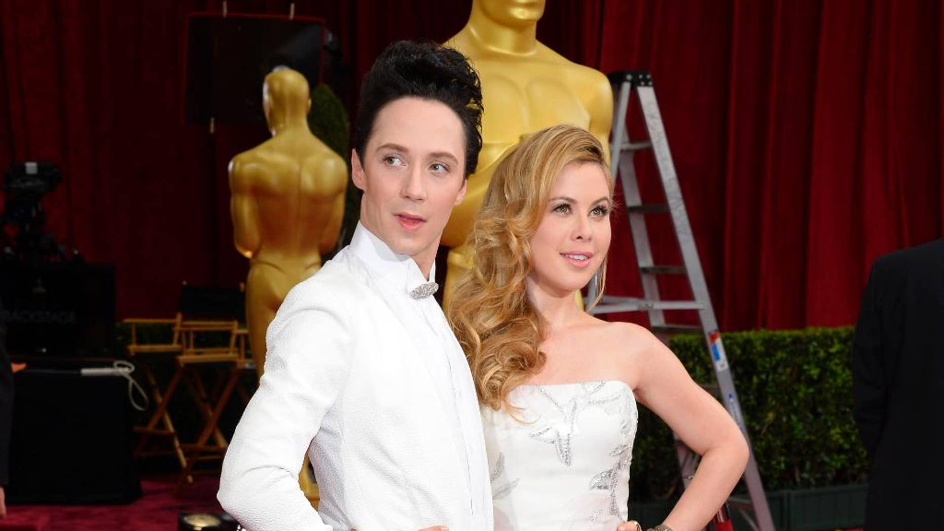 FILE - This March 2, 2014, file photo shows Johnny Weir, left, and Tara Lipinski at the Oscars in Los Angeles. NBC is promoting Weir and Lipinski to its top figure skating broadcasting team. The network said Wednesday, Oct. 22, 2014,  that the two former Olympians and play-by-play announcer Terry Gannon will take over the role starting with this week's Skate America.  (Photo by Dan Steinberg/Invision/AP, File)