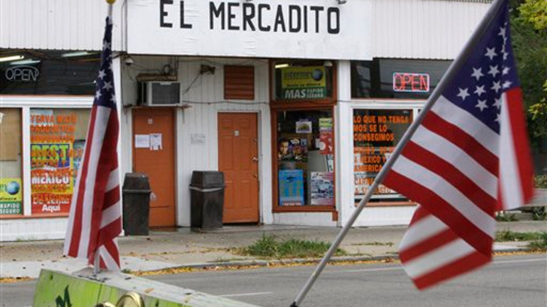 October 12: A pair of U.S. flags flies on a sign at a local lock business, across from a store aimed at attracting local immigrants in Dayton, Ohio.