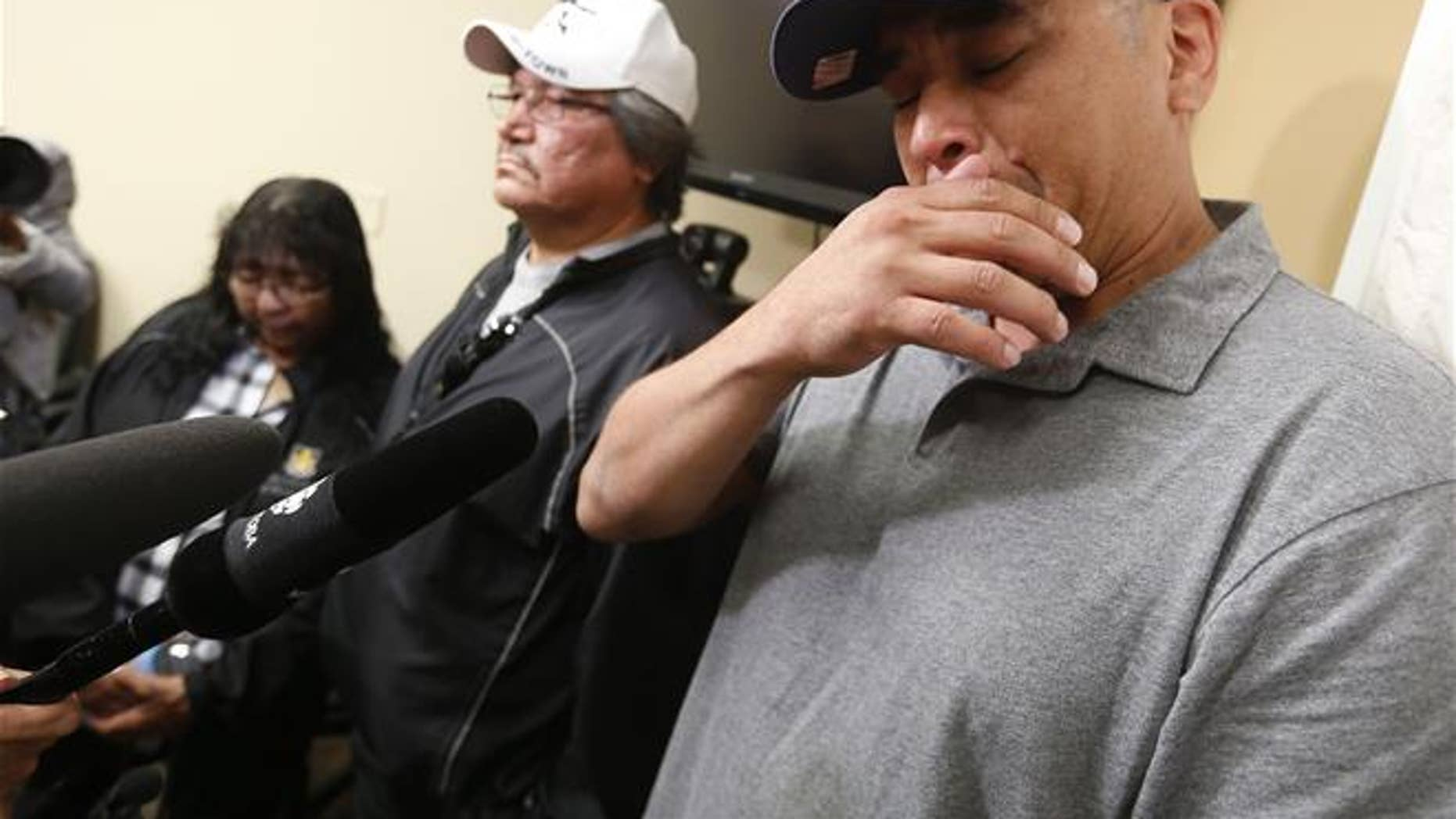Leon Swanson, right, with his mother Charlotte Mason and stepfather Henry Mason, weeps while speaking about being switched at birth earlier this year.