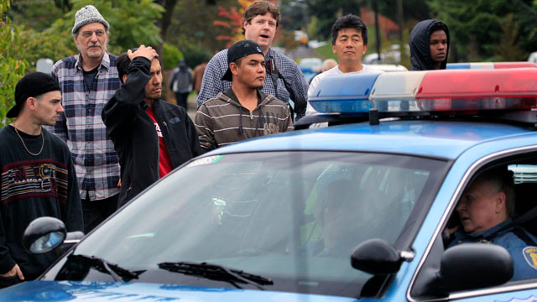 Neighbors look on at the scene of a shooting that left four people dead and another wounded Thursday, Sept. 23, 2010, in Seattle. The woman suspected of firing the shots at the southwest Seattle home apparently is among the dead. (AP Photo/Elaine Thompson)