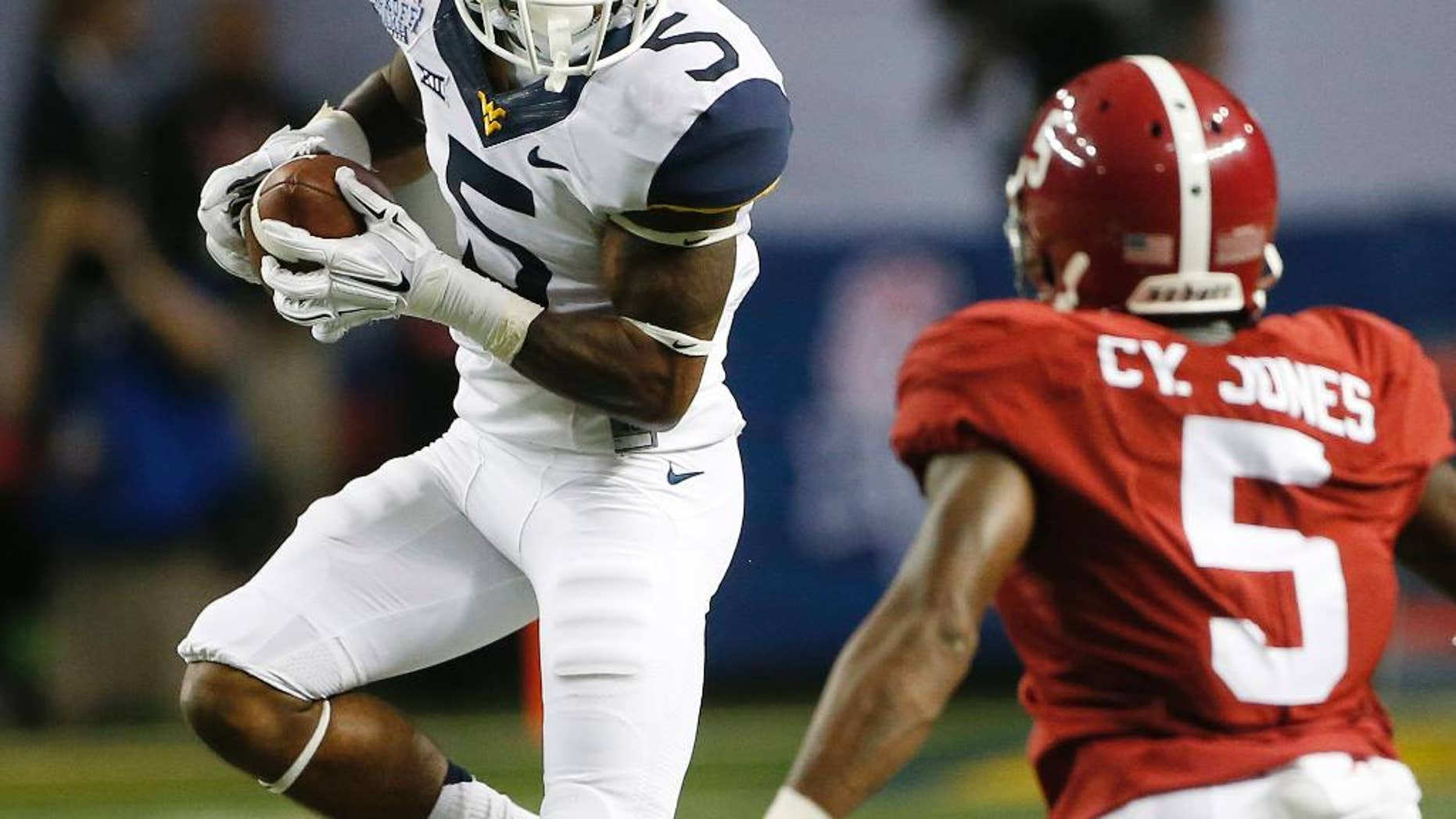 West Virginia wide receiver Mario Alford (5) makes a catch as Alabama defensive back Cyrus Jones (5) defends during the first half of an NCAA college football game Saturday, Aug. 30, 2014, in Atlanta.  (AP Photo/John Bazemore)