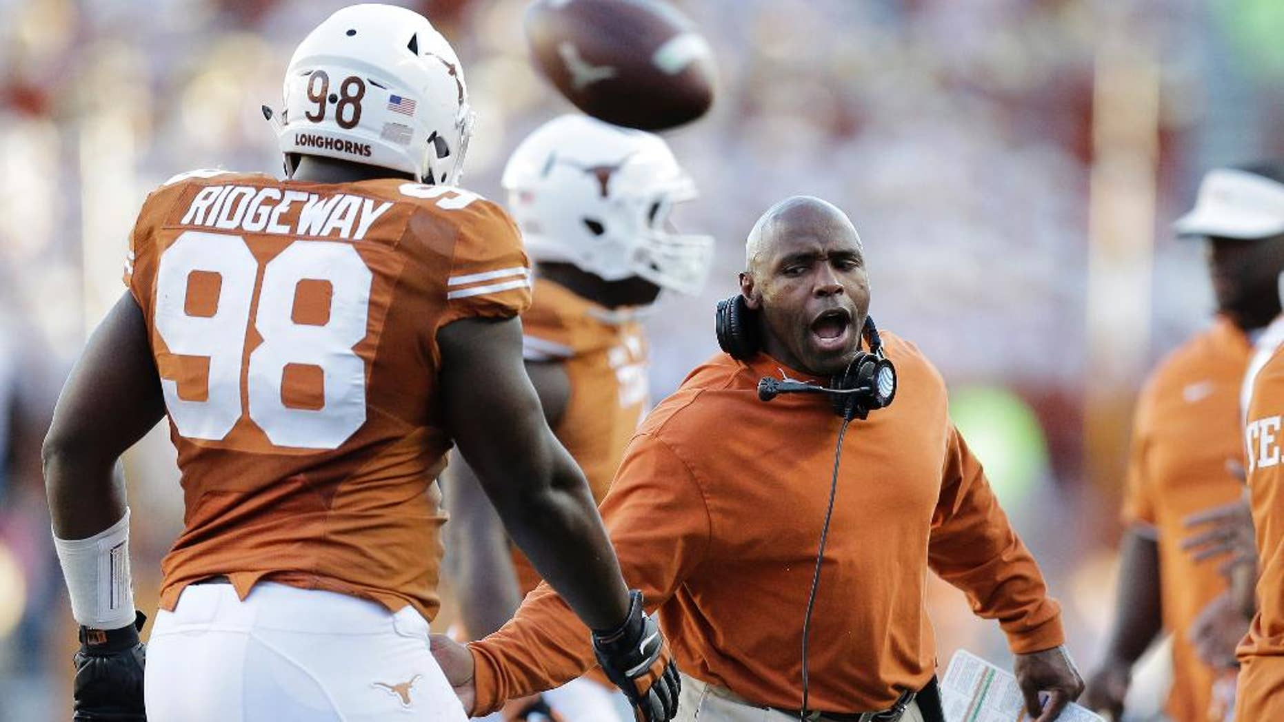 Texas Longhorns head coach Charlie Strong, right, congratulates players as they walk off the field during the second half of an NCAA college football game against West Virginia, Saturday, Nov. 8, 2014, in Austin, Texas.  Texas won 33-16. (AP Photo/Eric Gay)