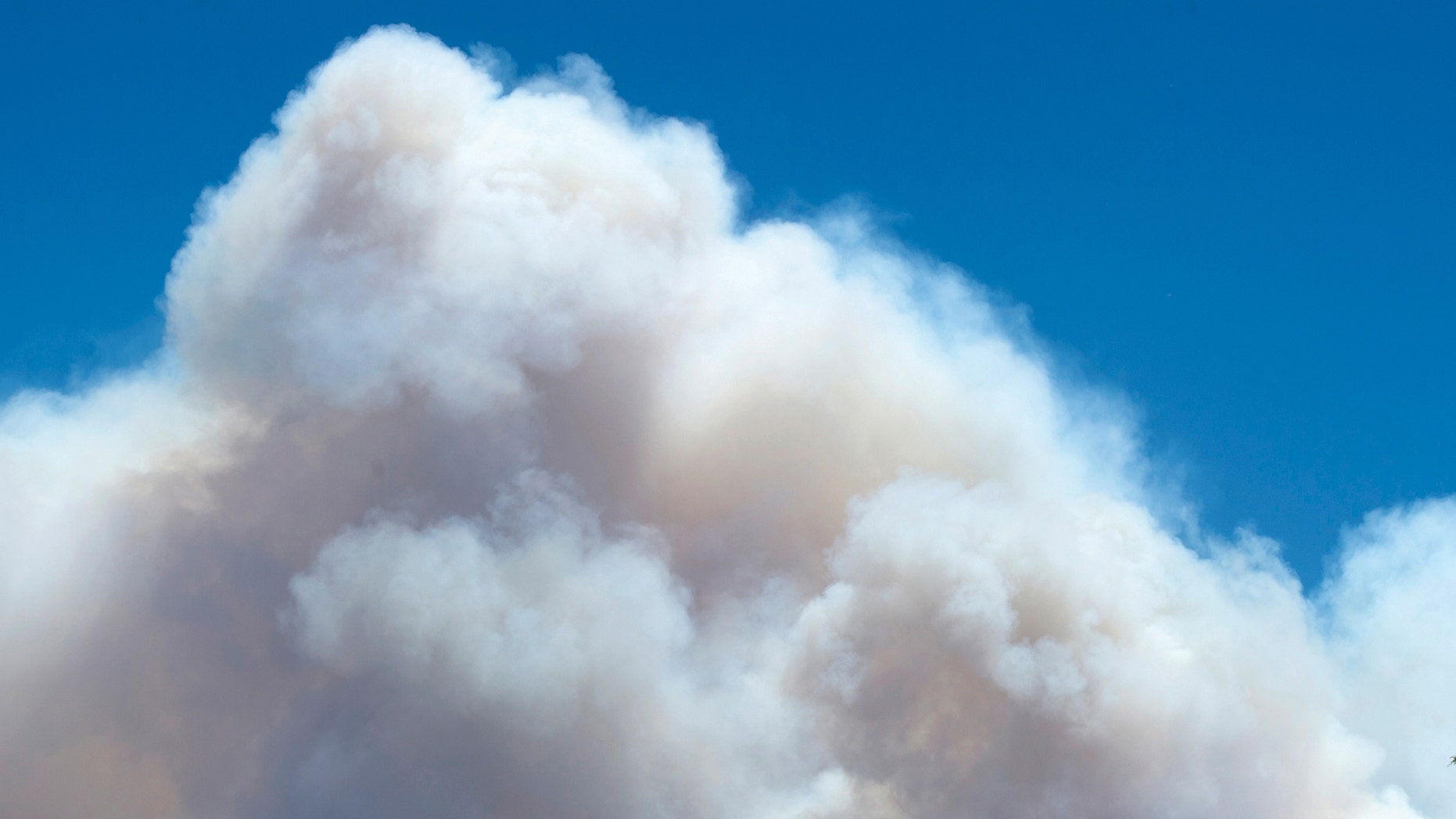 June 20, 2013: The smoke plume from the East Peak fire billows up behind a home on County Road 360 in La Veta, Colo.