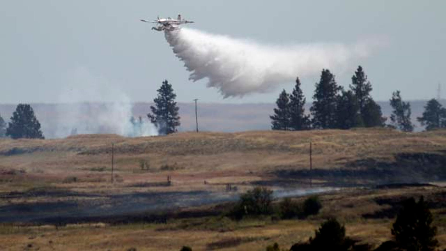 July 20, 2014: A firefighting plane drops water from Fishtrap Lake on a stubborn fire burning near the lake in Lincoln County near Cheney, Wash.  (AP Photo/The Spokesman-Review, Jesse Tinsley)