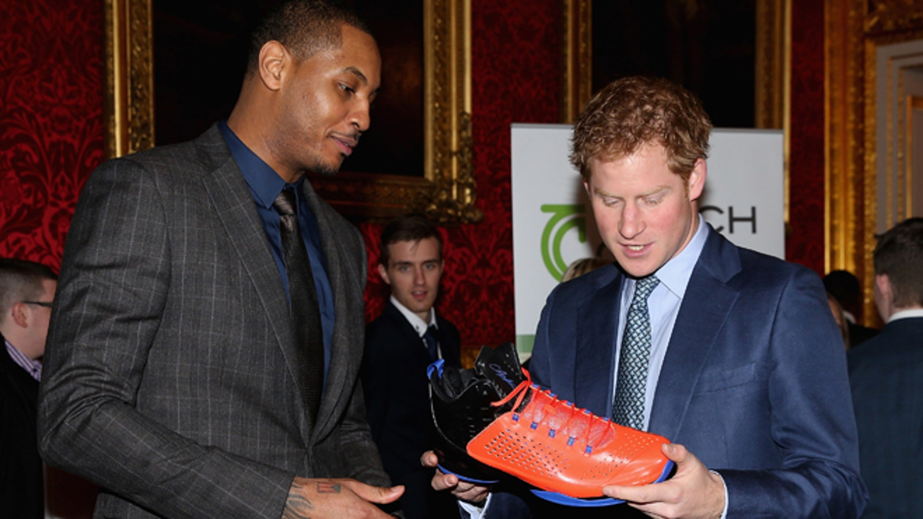 Britain's  Prince Harry, right,  is presented with a basketball shirt and size 15 basketball shoe by NBA All-Star Carmelo Anthony, during a Coach Core Graduation event at St James's Palace, in London, Wednesday, Jan. 14, 2015. The Coach Core model, a year's apprenticeship, aspires to produce well qualified sports coaches to work in the community. (AP Photo/ Chris Jackson, Pool)