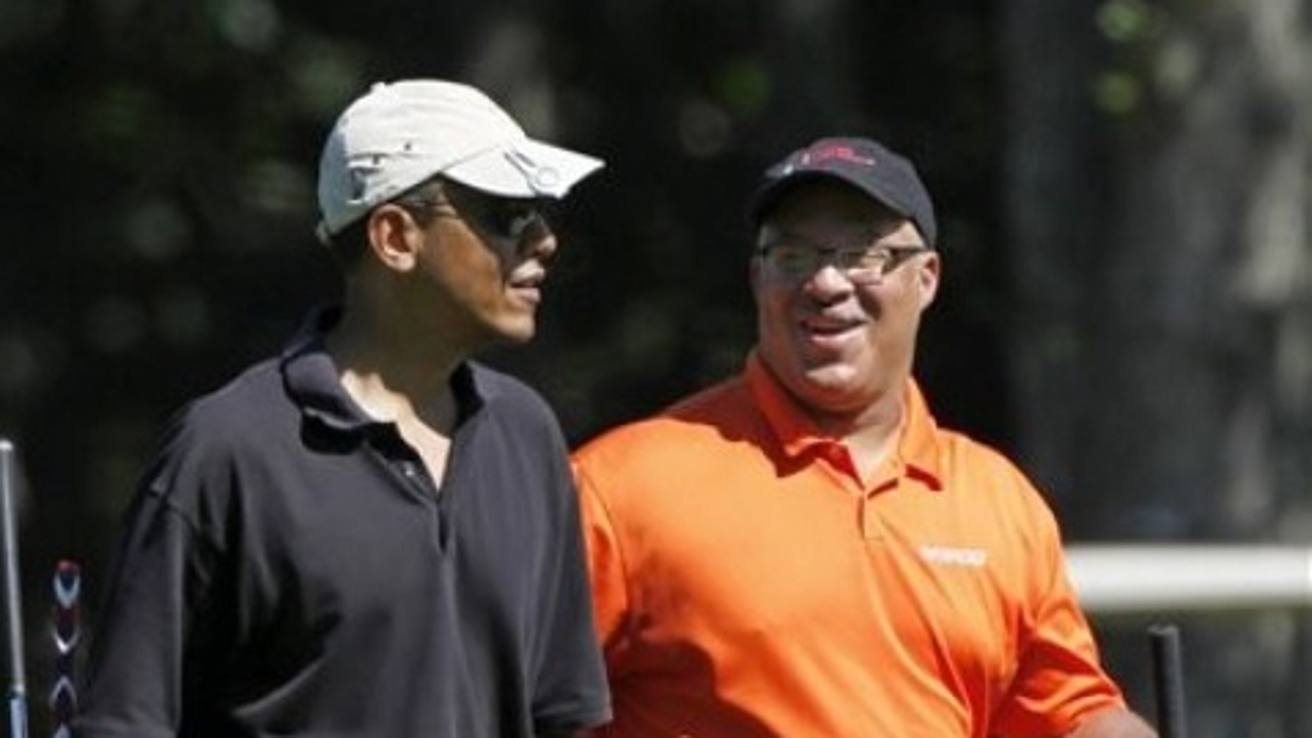 File: Aug. 23, 2011: President Barack Obama plays golf with Dr. Eric Whitaker on the island of Martha's Vineyard, in Massachusetts.