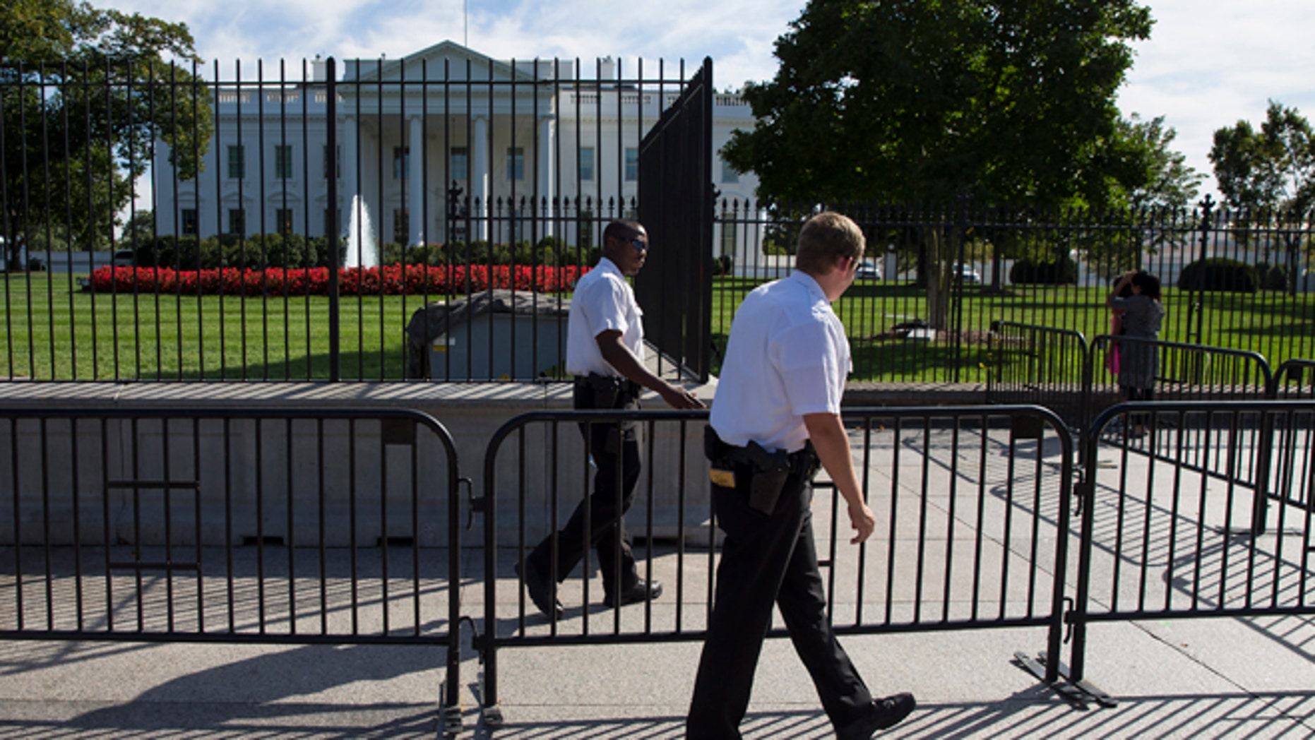 In this Monday, Sept. 22, 2014 photo, Secret Service police officers walk outside the White House in Washington.