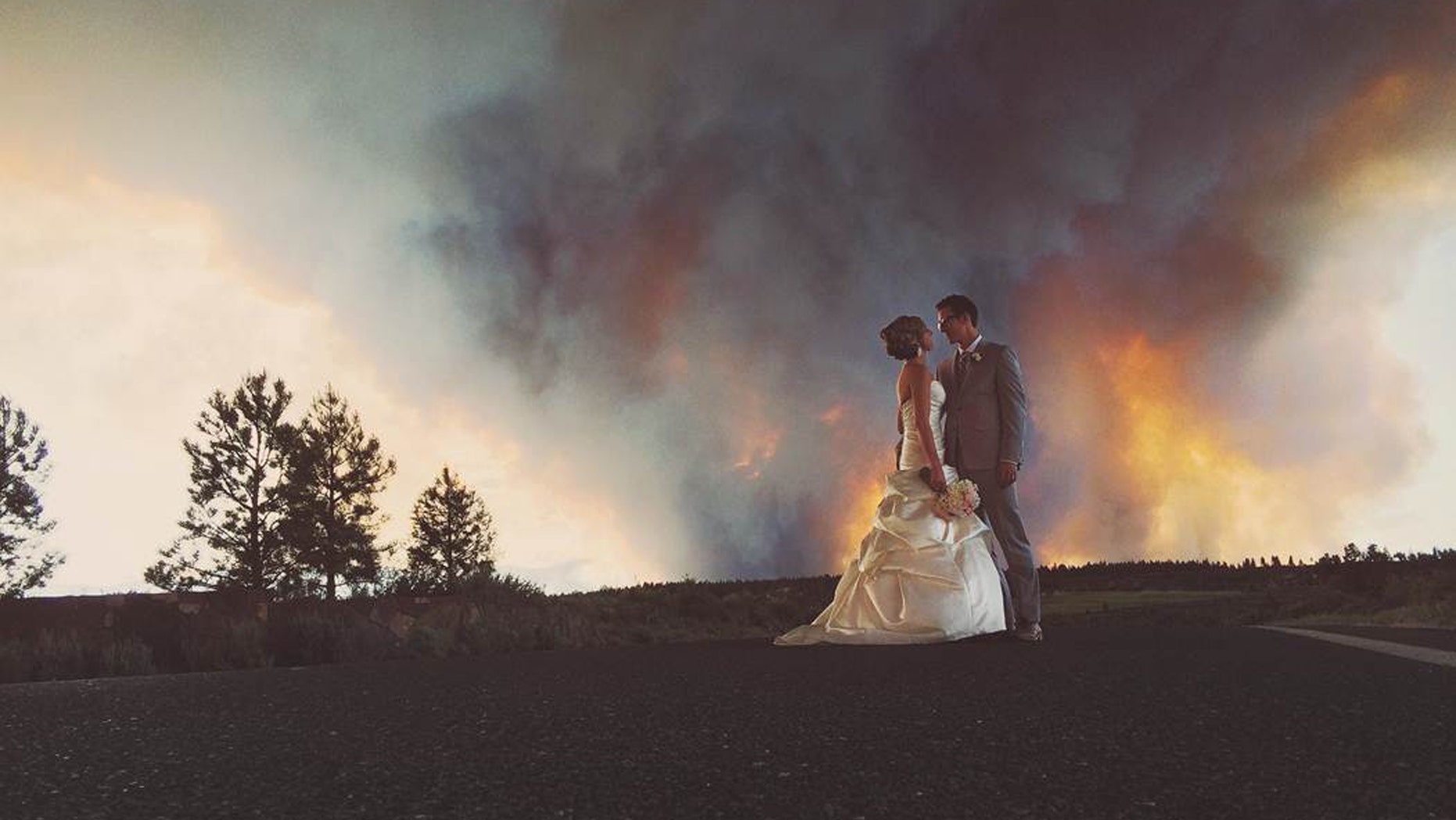 In this Saturday, June 7, 2014 photo provided by Josh Newton, newlyweds Michael Wolber and April Hartley pose for a picture near Bend, Ore., as a wildfire burns in the background. Because of the approaching fire, the minister conducted an abbreviated ceremony and the wedding party was evacuated to a downtown Bend park for the reception. (AP/Josh Newton)
