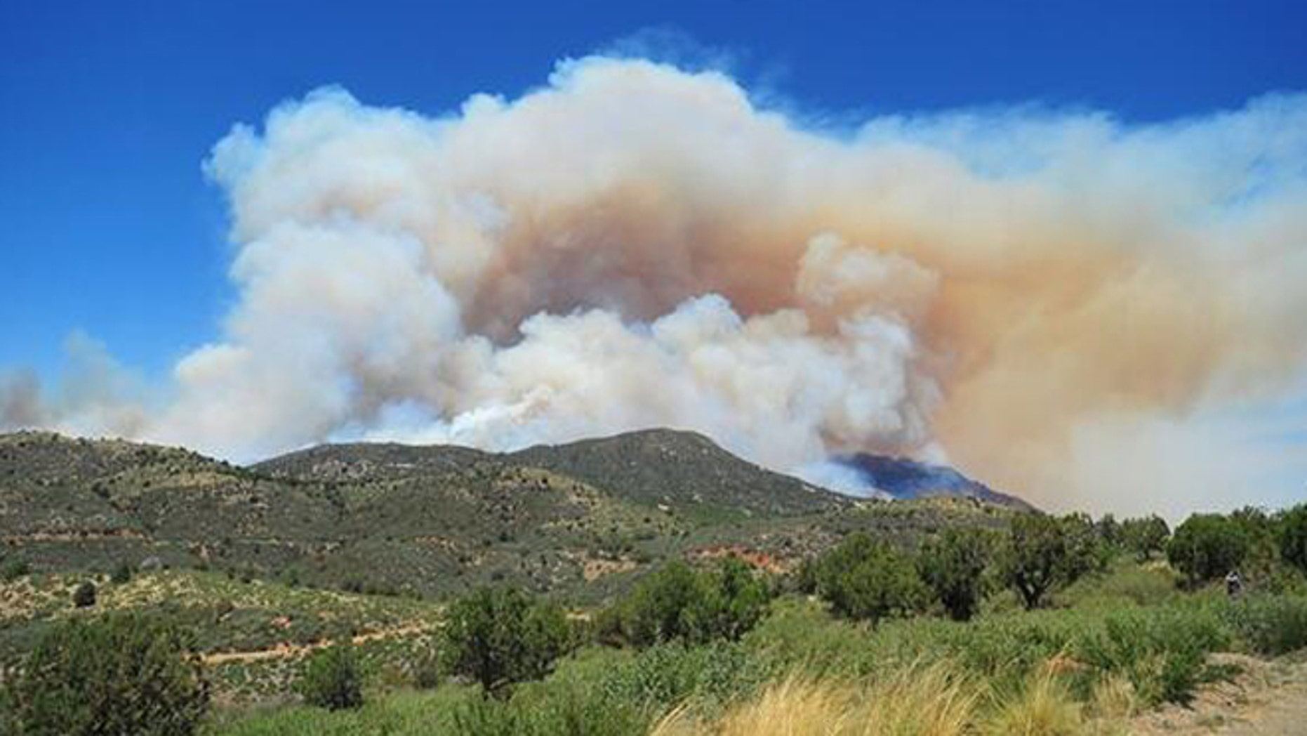June 18, 2013: Smoke rises as the Doce Fire burns near Prescott, Ariz. on Tuesday. County sheriff's officials say the wildfire began midday Tuesday near the Doce Pit about eight miles northwest of Prescott. Wind gusts of up to 22 mph pushed the fire from 20 acres to about 200 within an hour.