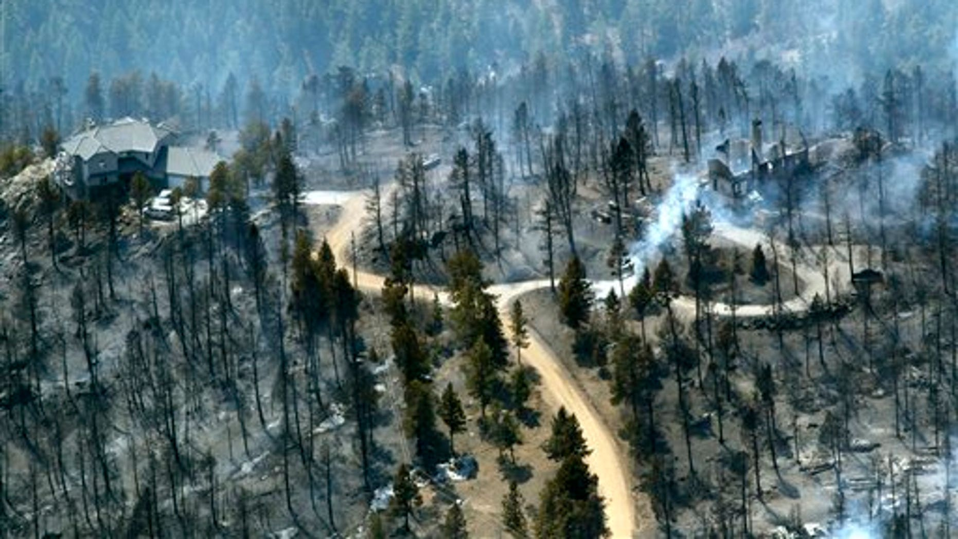 March 27: One home stands untouched at left while another home at right smolders after burning in the Lower North Fork Wildfire in the foothills community of Conifer, Colo., southwest of Denver.