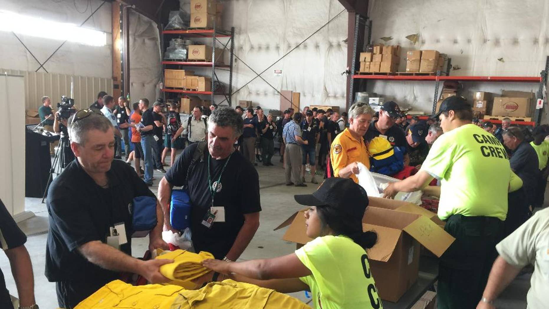 Warren Heslip, 47, of Southland, New Zealand, receives a yellow firefighting shirt on Monday, Aug. 24, 2015 at the National Interagency Fire Center in Boise, Idaho. Australian and New Zealand firefighters have arrived in the United States and prepared to fan out to help fight wildfires burning in several western states. (AP Photo/Keith Ridler)