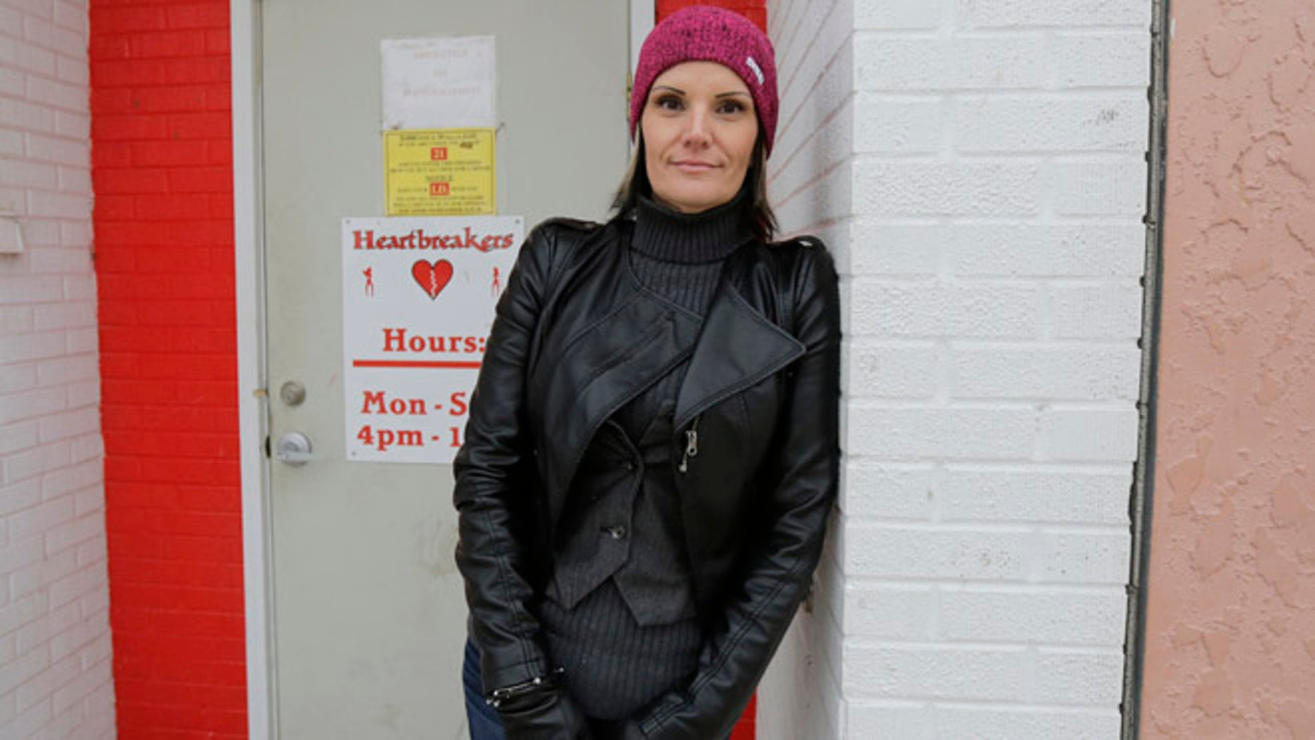 Dec. 16, 2014: Windie Lazenko, with the anti-trafficking group 4her North Dakota, stands for a photo in front of a club in Williston, N.D. As a 13-year-old runaway, Lazenko says she was bought and sold for sex. Prostitution, pornography and strip clubs followed. Then she walked away from it all.