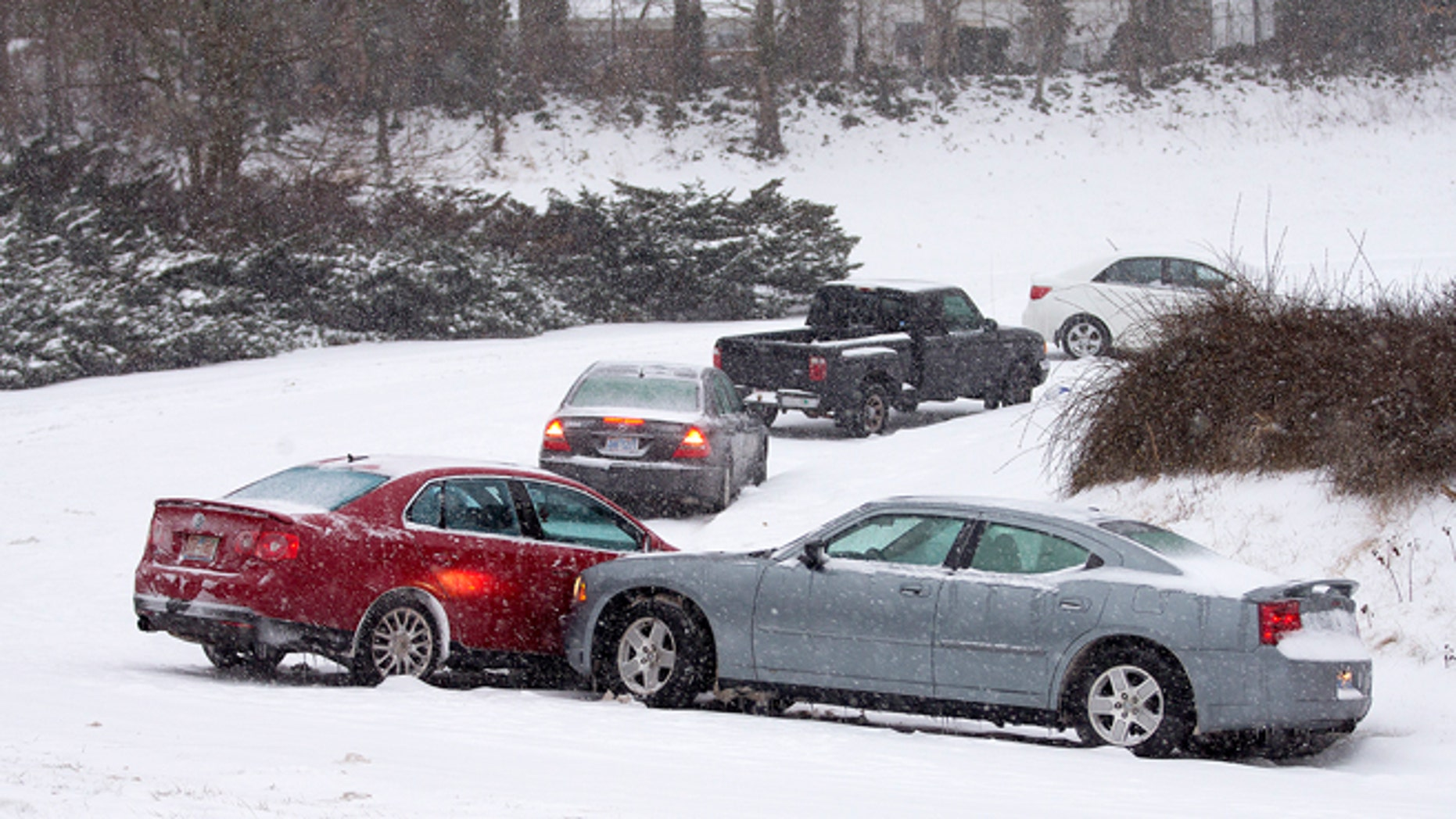 Cars that lost traction sit on the eastbound ramp from Joseph Bryan Boulevard to Holden Road during a snowfall in Greensboro, N.C., Wednesday, Feb. 12, 2014. A major winter slammed into North Carolina Wednesday, turning homebound commutes that typically take minutes into hours-long ordeals as traffic slowed to a slippery slog and threatening to leave many areas dark because of power outages. (AP Photo/News & Record, Nelson Kepley)