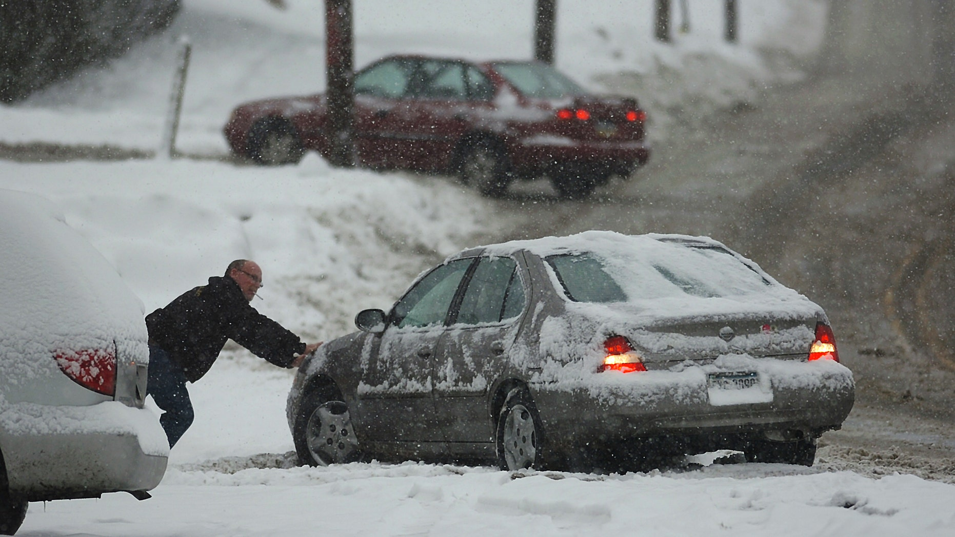 A resident helps out a motorist push his car out of the snow on an icy West Lackawanna Avenue in Blakely,  Pa. on Saturday, Dec. 29, 2012. Snow from a mild but widespread winter storm began falling Saturday over most of the Northeast and the upper Ohio River Valley, the second in less than a week for the regions. (AP Photo/Scranton Times & Tribune, Butch Comegys)  WILKES BARRE TIMES-LEADER OUT; MANDATORY CREDIT