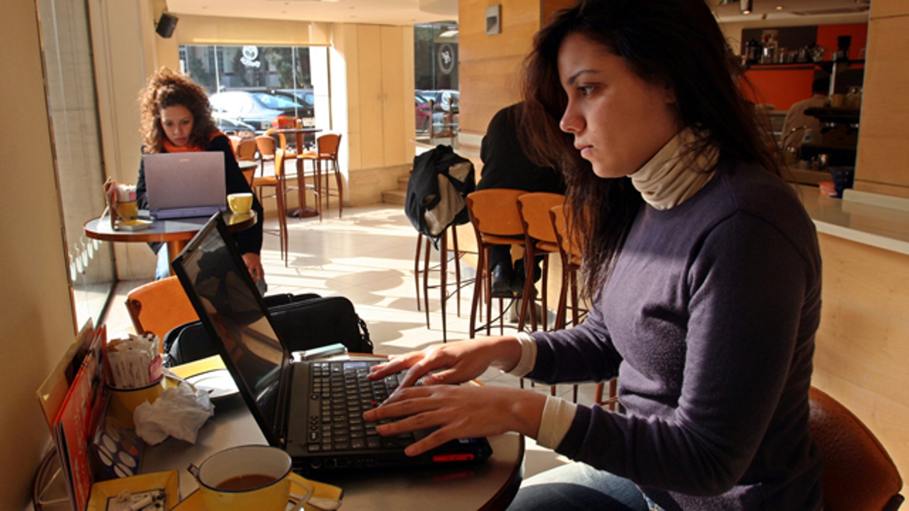 FILE: Egyptians work on their computers in a cafe in Cairo.