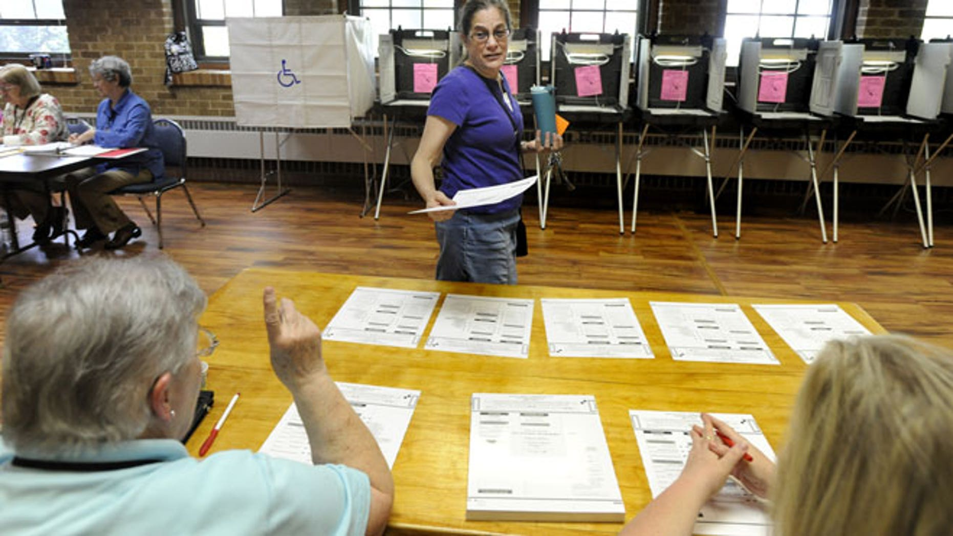 May 8, 2012: Ruth Hoover talks with poll volunteer workers Fay Tichy, left, and Jacki Helgerson, right, after receiving her ballot from them prior to voting in the Wisconsin recall primary election in the Union Grove Municipal building in Union Grove, Wis.