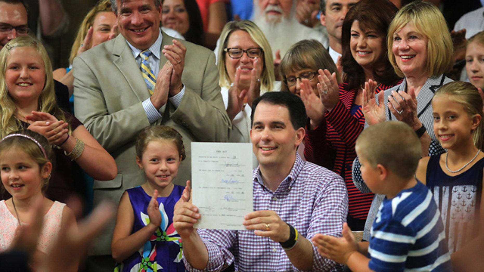 July 12, 2015: Wisconsin Governor Scott Walker displays a signed 2015-2017 state budget during a ceremony on the production floor of Valveworks USA in Waukesha, Wis. (John Hart/Wisconsin State Journal via AP)
