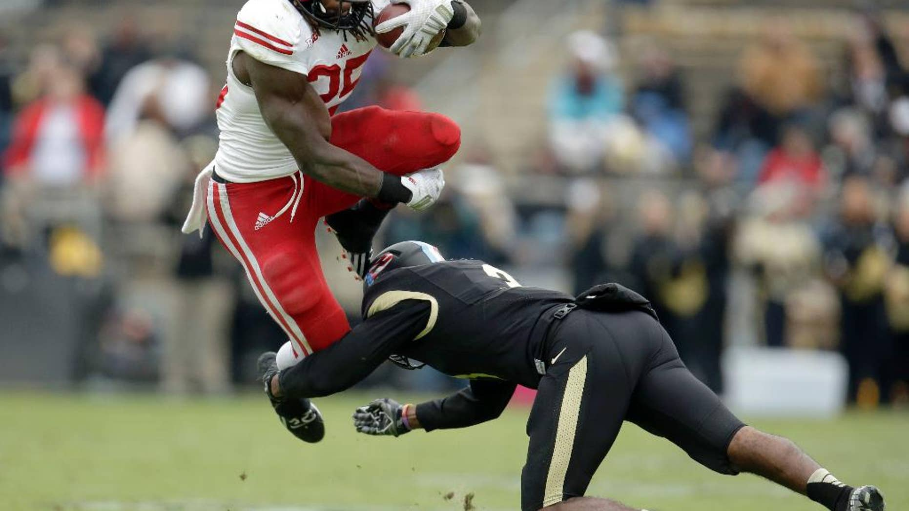 Wisconsin running back Melvin Gordon, left, leaps to avoid a tackle by Purdue defensive back Leroy Clark during the second half of an NCAA college football game in West Lafayette, Ind., Saturday, Nov. 8, 2014. Wisconsin won 34-16. (AP Photo/AJ Mast)